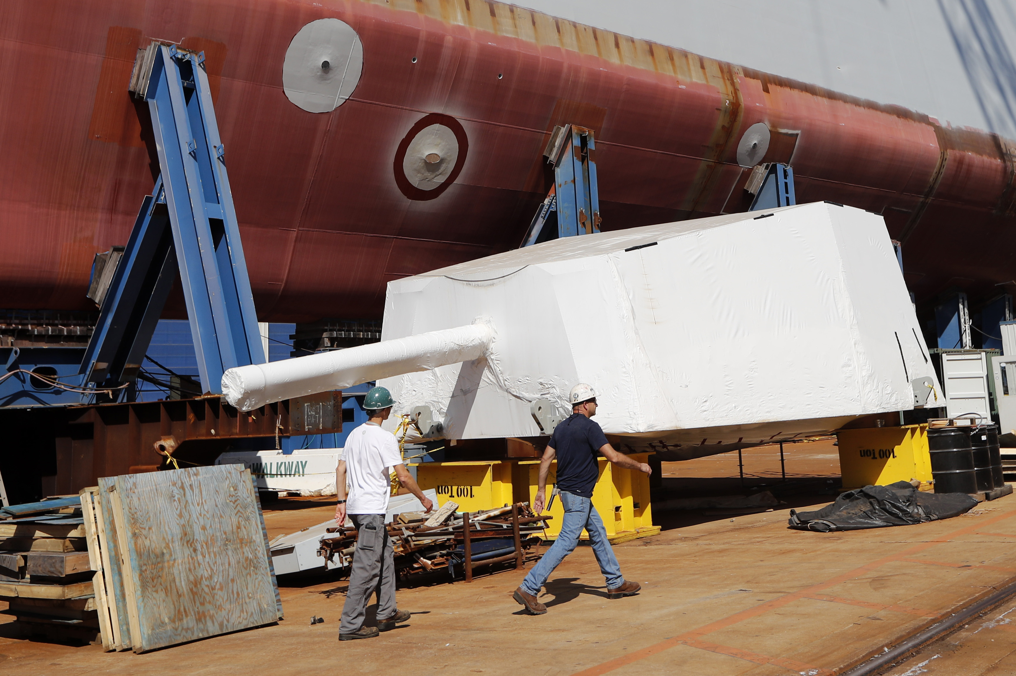 Workers walk by the Advanced Gun System, covered in shrink wrap, alongside a Zumwalt-class destroyer being built in the shipyard at Bath Iron Works in Bath, Maine, on Aug. 29, 2018.