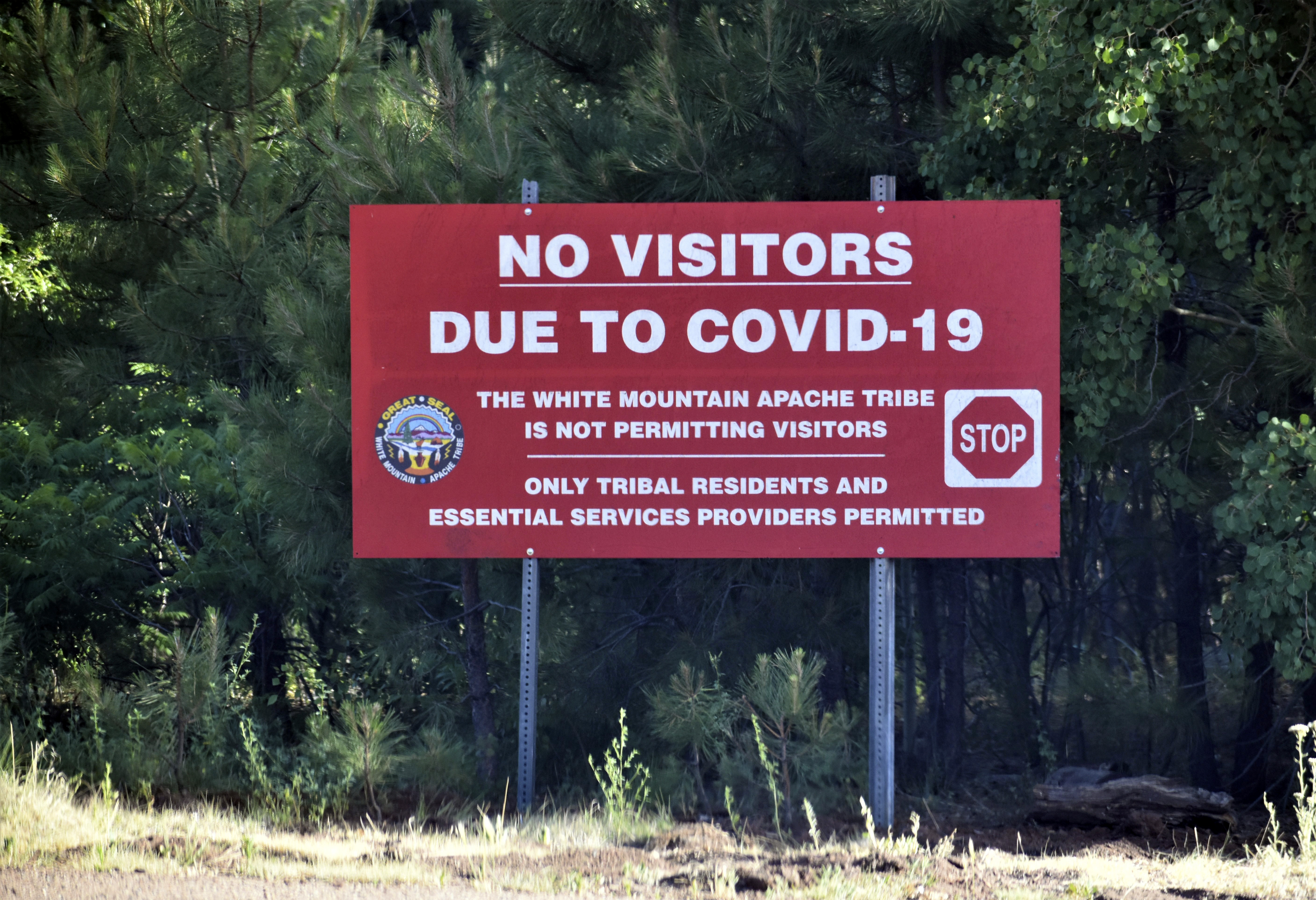 In this Thursday, June 25, 2020 photo provided by C.M. Clay, a sign alerts motorists that visitors are not allowed on the Fort Apache Indian Reservation in eastern Arizona on June 25, 2020.