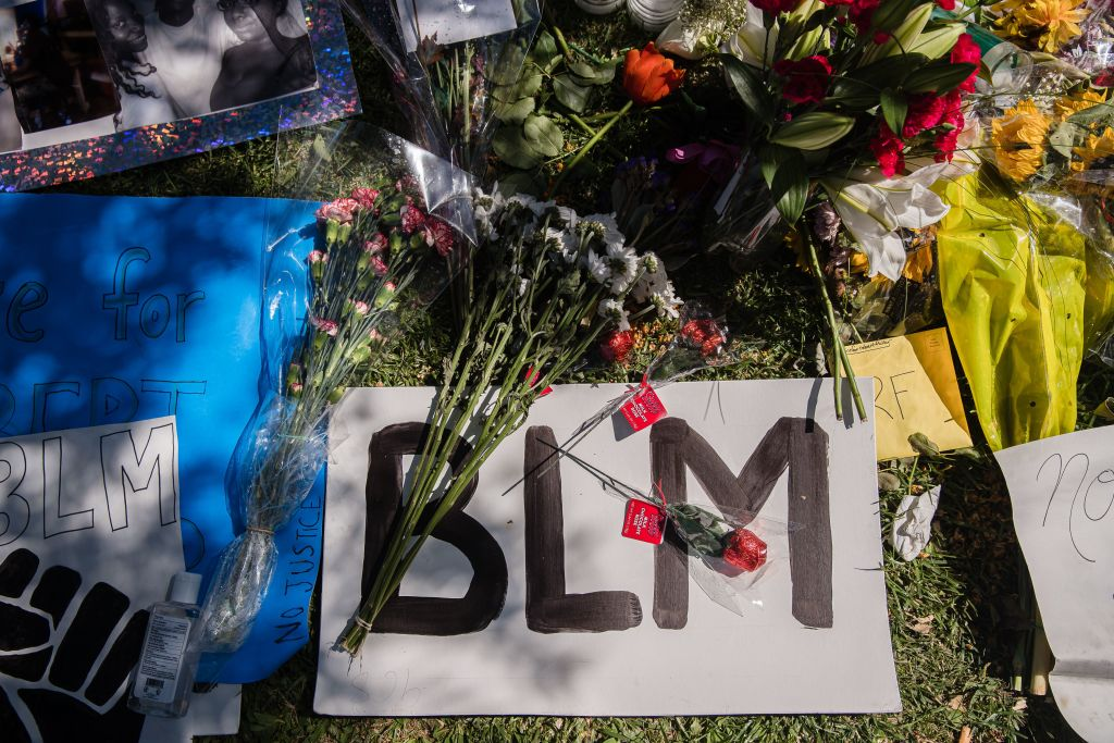 A Black Lives Matter sign and flowers can be seen on the ground at a makeshift memorial at Palmdale City Hall for Robert Fuller, a young black man who was found hanging from a tree, on June 16, 2020, in Palmdale, California.