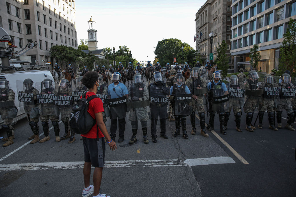 Security forces block the road as protesters gather near Lafayette Park ahead of President Trump's trip to St. John's Church in Washington, United States on June 2, 2020. Protests and riots continue in cities across US following the death of George Floyd, an unarmed black man who died after being pinned down by a white police officer.