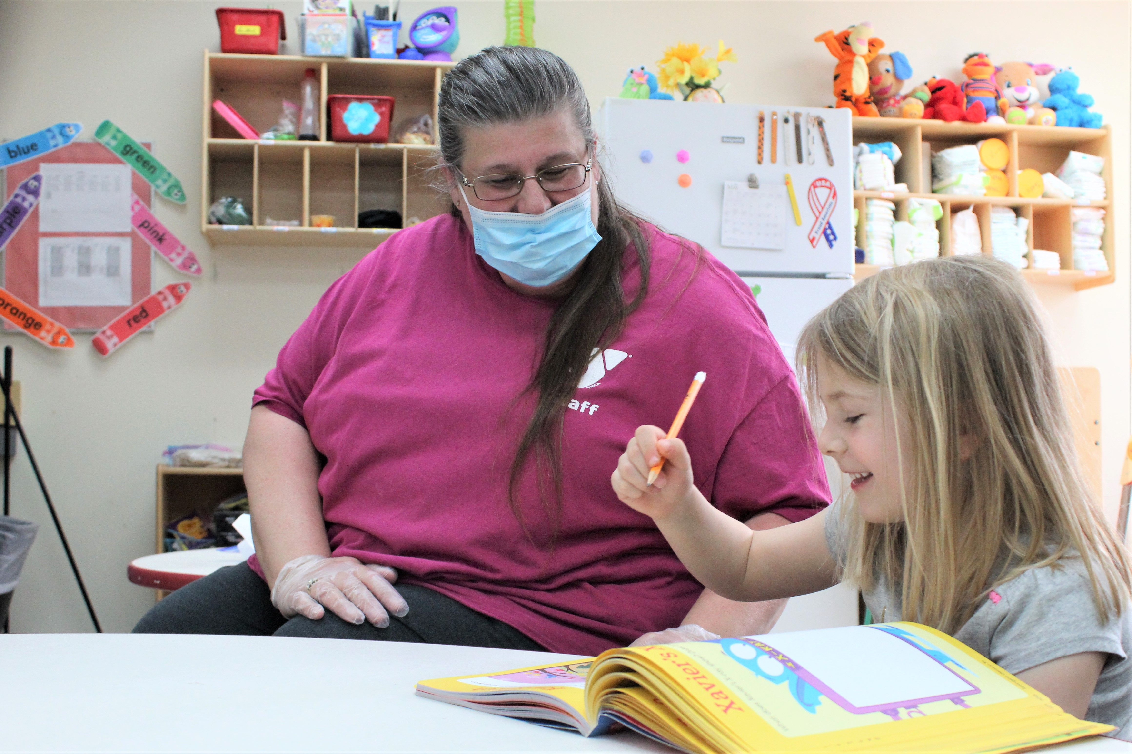 YMCA childcare provider Darlene Mount wears a mask and gloves to keep children safe amid the 2020 coronavirus pandemic