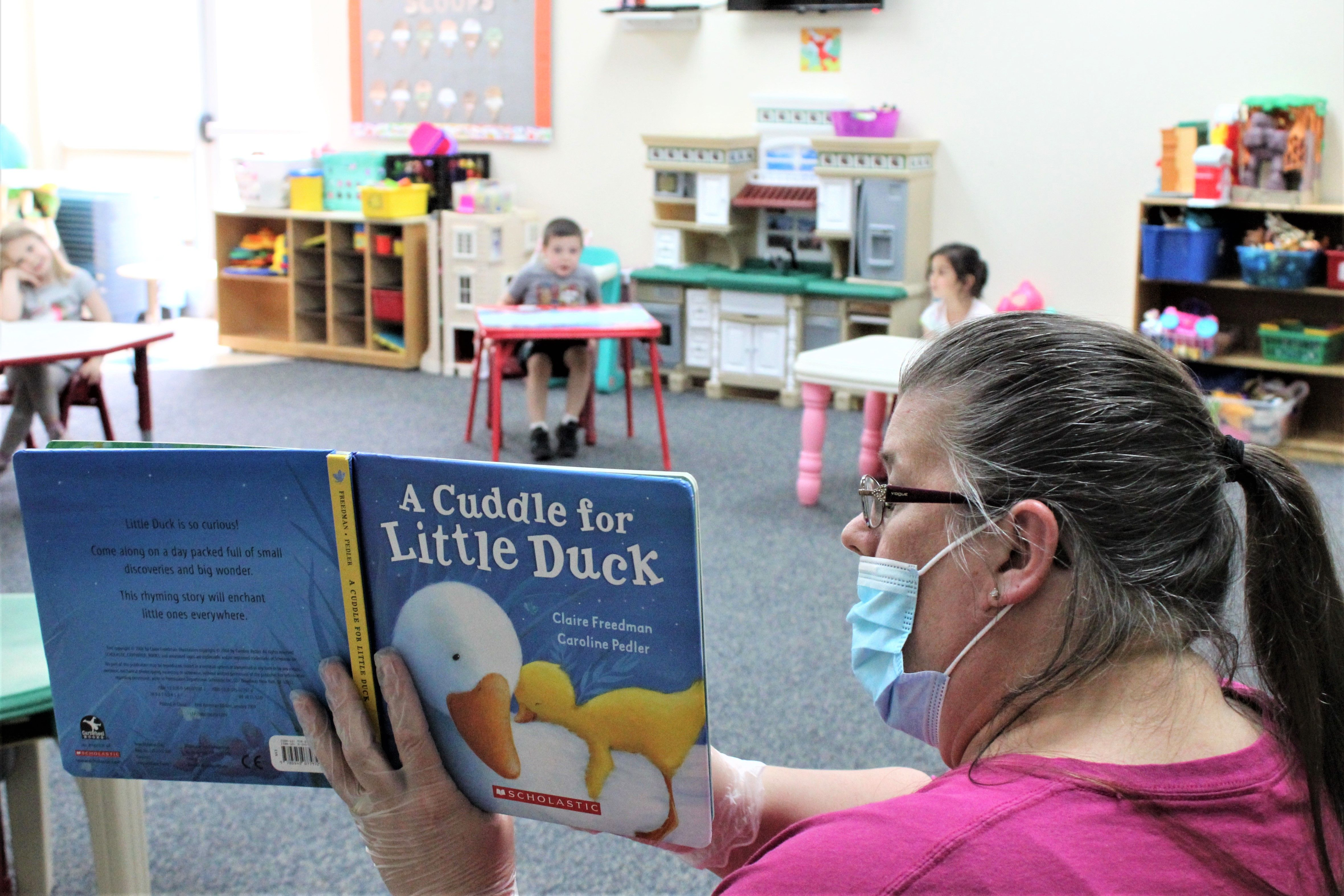 Daycare provider Darlene Mount reads a book to children at a New Jersey YMCA during the ongoing COVID-19 pandemic. The children are in a modified circle that allows for proper social distancing.