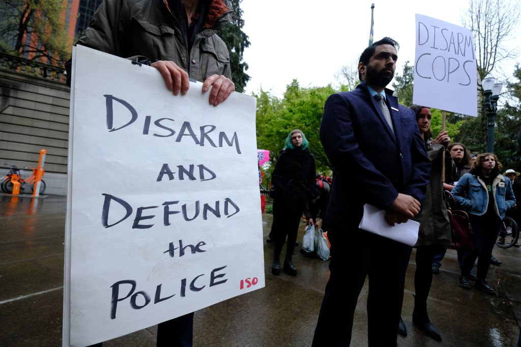 A protester holds a sign reading  Disarm And Defund The Police  during a protest against fatal police shootings in Portland, Oregon, United States on April 11, 2018. John Andrew Elifritz, 48, was fatally shot by police after he reportedly fled from a stolen car and burst into a homeless shelter at the start of an alcoholics anonymous meeting last Saturday.
