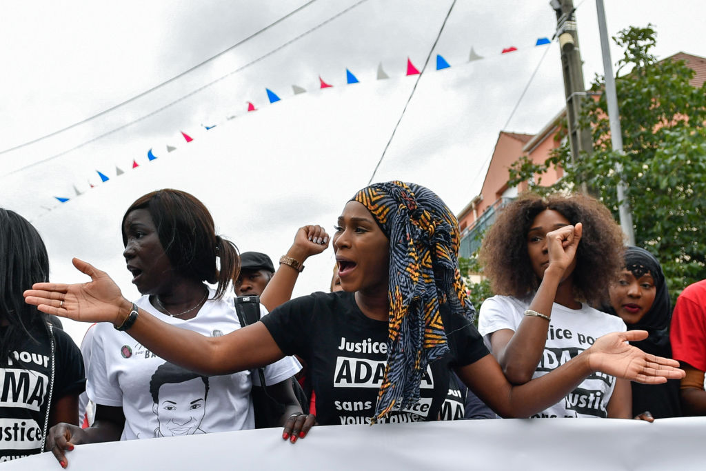 Assa Traore (C), the elder sister of late Adama Traore, who died during his arrest by the police in July 2016, wearing a tee-shirt reading 'Justice for Adama, without justice, you won't have peace' delivers a speech during a commemorative march on July 22, 2017 in Beaumont-sur-Oise, northeast of Paris.