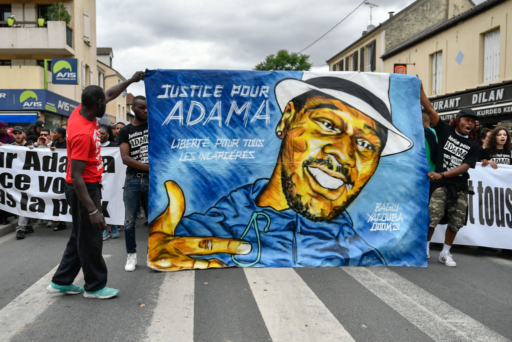 People raise their fists as they take part in a march in memory of Adama Traore, who died during his arrest by the police in July 2016, on July 22, 2017 in Beaumont-sur-Oise, northeast of Paris.