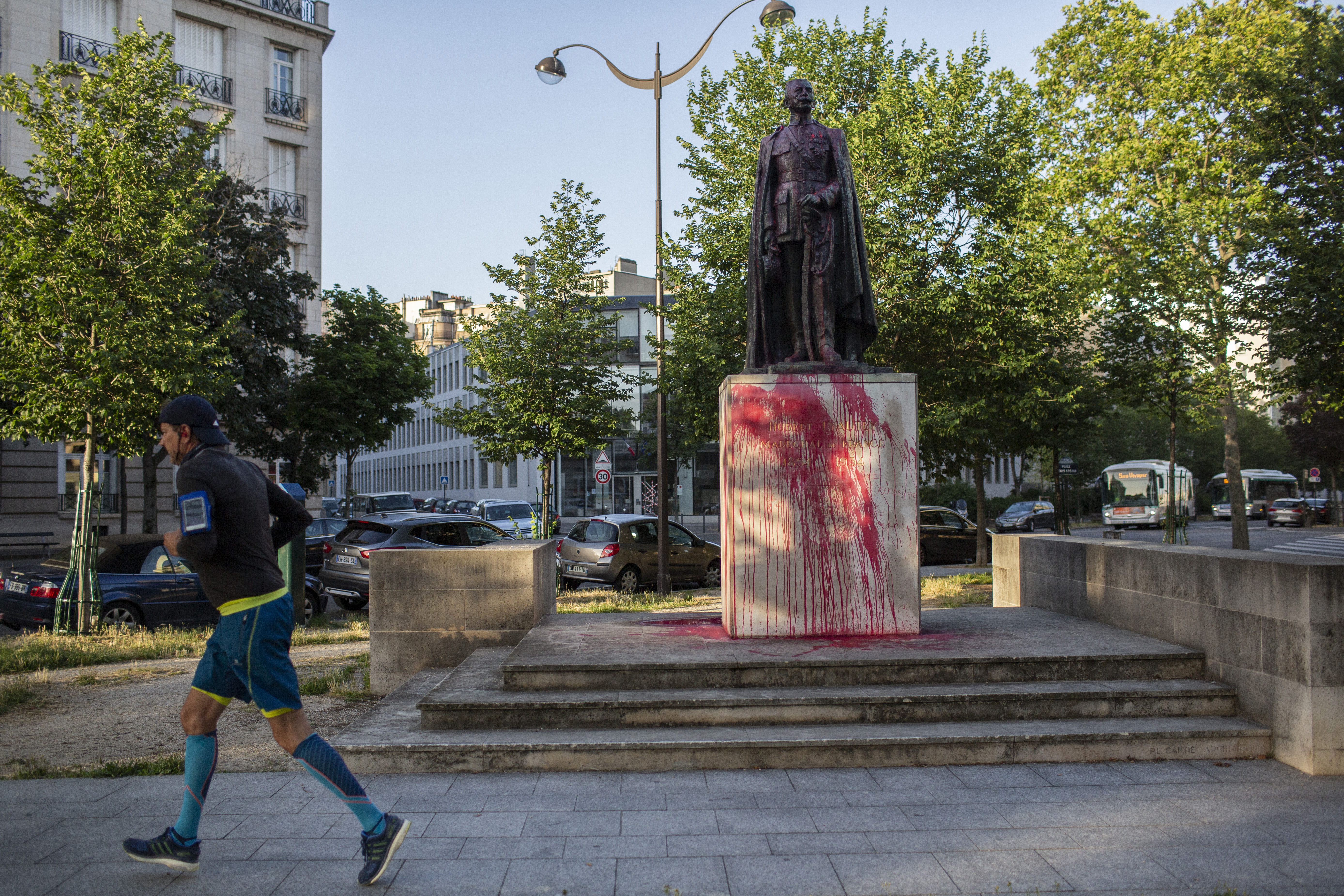 A man jogs past a statue, covered with red painting, of Hubert Lyautey, who served in Morocco, Algeria, Madagascar and Indochina when they were under French control, on June 22, 2020.