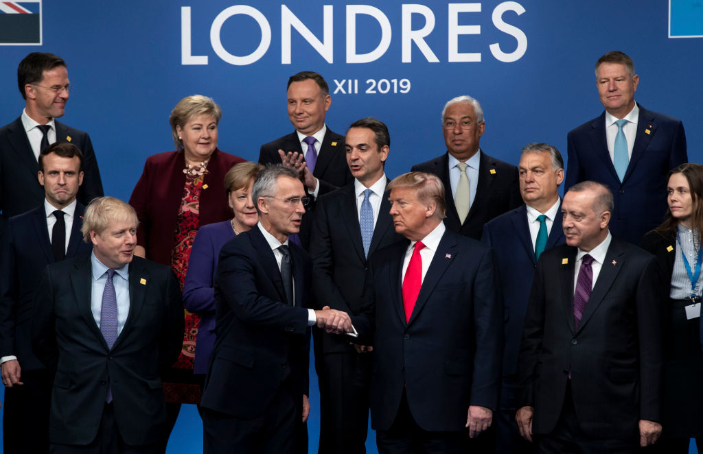 NATO Secretary General Jens Stoltenberg shakes hands with U.S. President Donald Trump during a group photo at NATO North Atlantic Treaty Organisation Summit in London on Dec. 4, 2019.