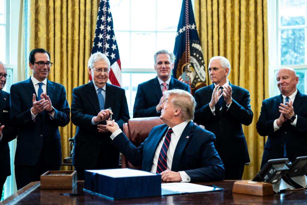President Trump gives a pen to Senate Majority Leader Mitch McConnell during a bill signing ceremony for the CARES Act in the Oval Office