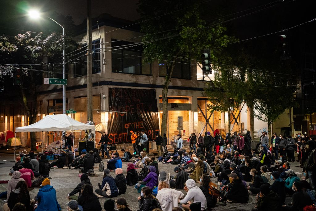 People sit in the street while watching a documentary film screening outside of the Seattle Police Departments East Precinct on June 9, 2020 in Seattle, Washington.
