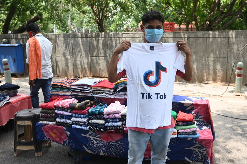 A garment street vendor poses for a picture in front of his stall with a t-shirt with the logo of the social media video-sharing application Tik Tok in New Delhi on June 30, 2020.