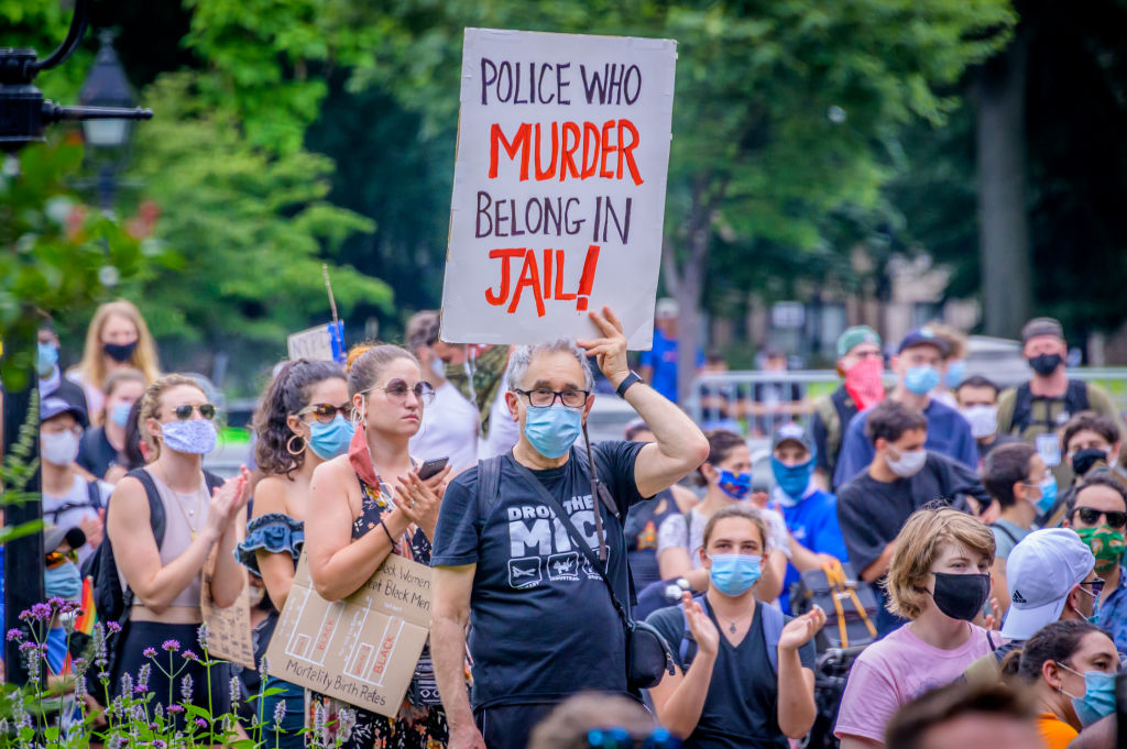 A participant holding a sign during a march to City Hall in support of the #OccupyCityHall action for NYPD budget cuts  in Manhattan, New York, on June 29, 2020.