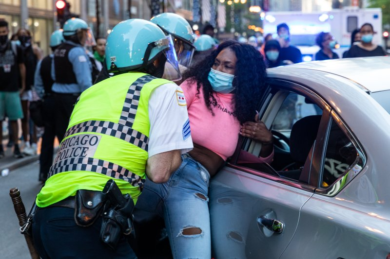 Police officers arrest a woman during protests in Chicago on May 30 following the killing of George Floyd by Minneapolis police.