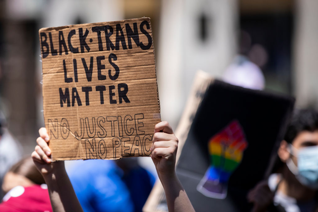 A Caucasian protester holds up their homemade sign on a box that says,  Black Trans Lives Matter No Justice No Peace  during a protest at Trump Tower in the Manhattan Borough of New York on June 12, 2020.