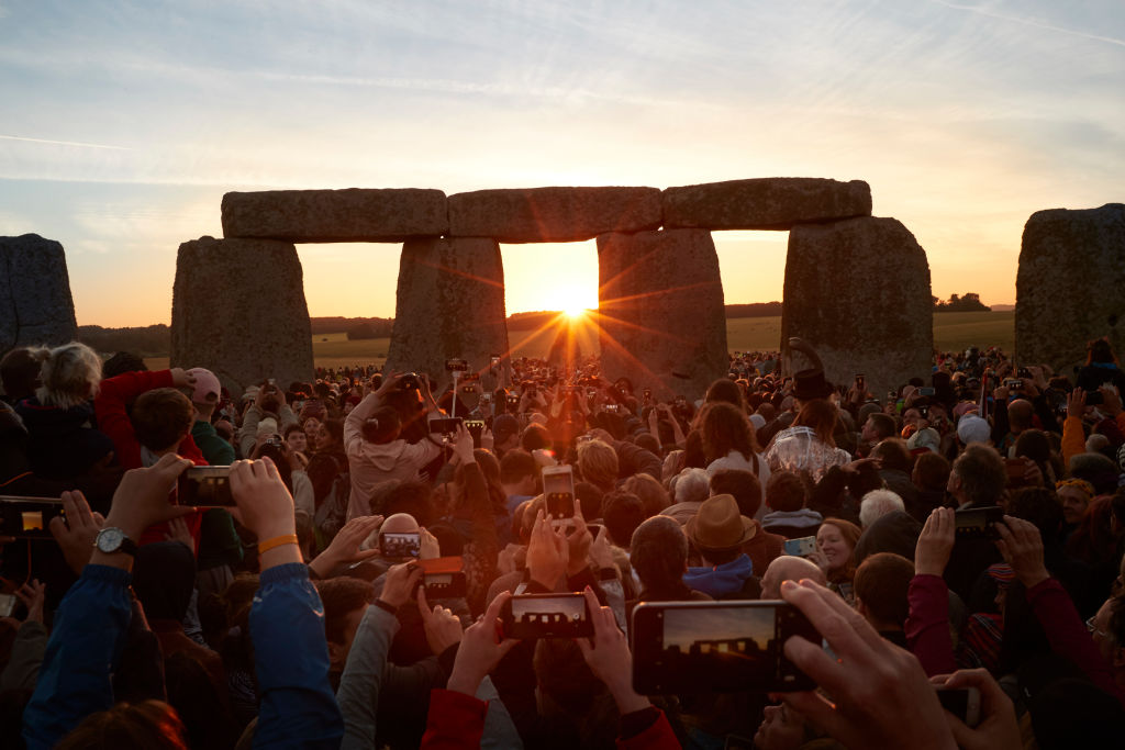The sun rises over the horizon at the ancient Stone circle of Stonehenge on June 21, 2018 in Wiltshire, England. Celebrations were cancelled this year due to bans on mass gatherings as a result of COVID-19
