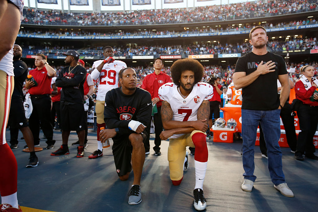 Eric Reid #35 and Colin Kaepernick #7 of the San Francisco 49ers kneel on the sideline during the anthem, as free agent Nate Boyer stands, prior to the game against the San Diego Chargers at Qualcomm Stadium on September 1, 2016 in San Diego, California.
