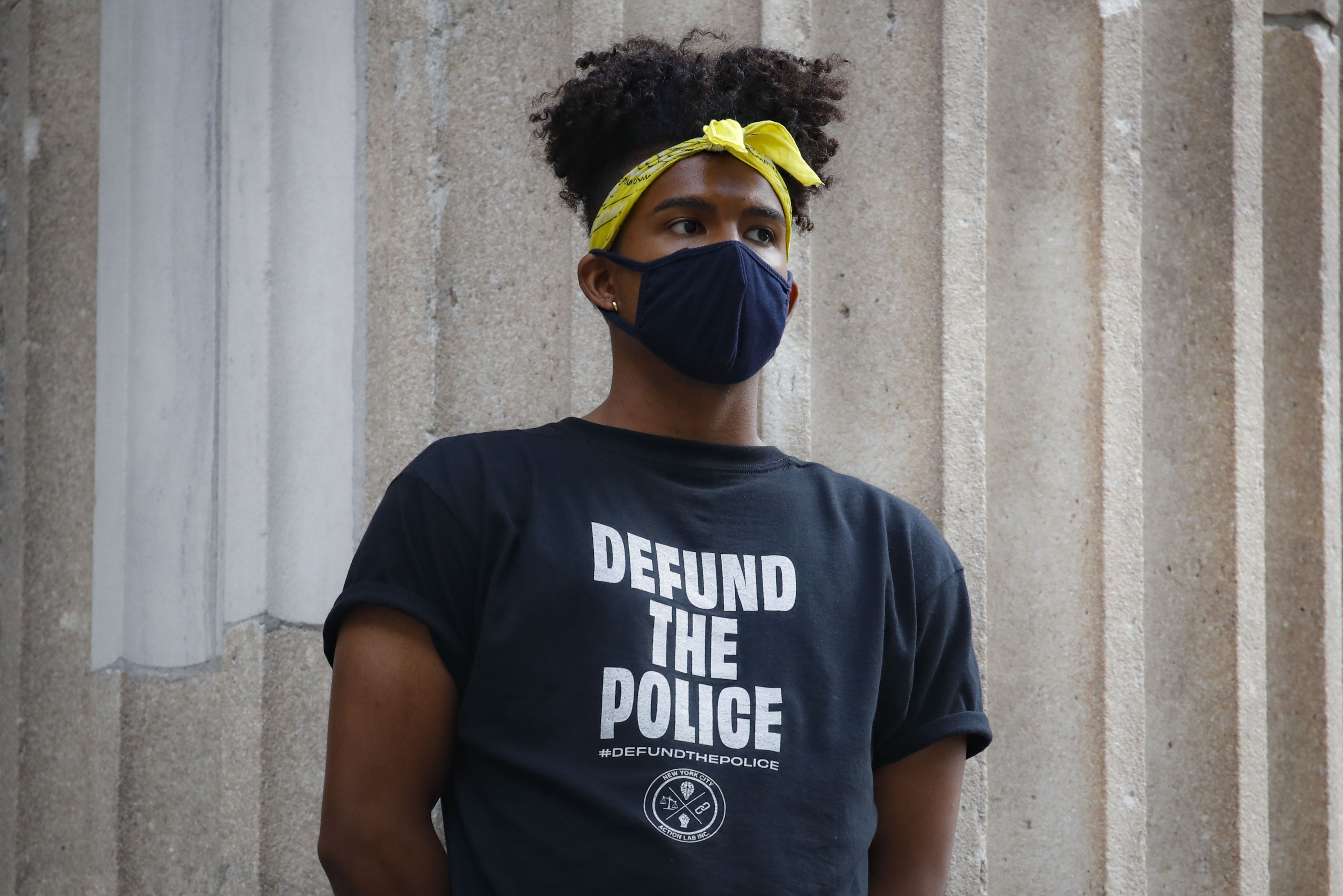 A protester stands on the steps of a government building near an encampment outside City Hall in New York on June 30, 2020.