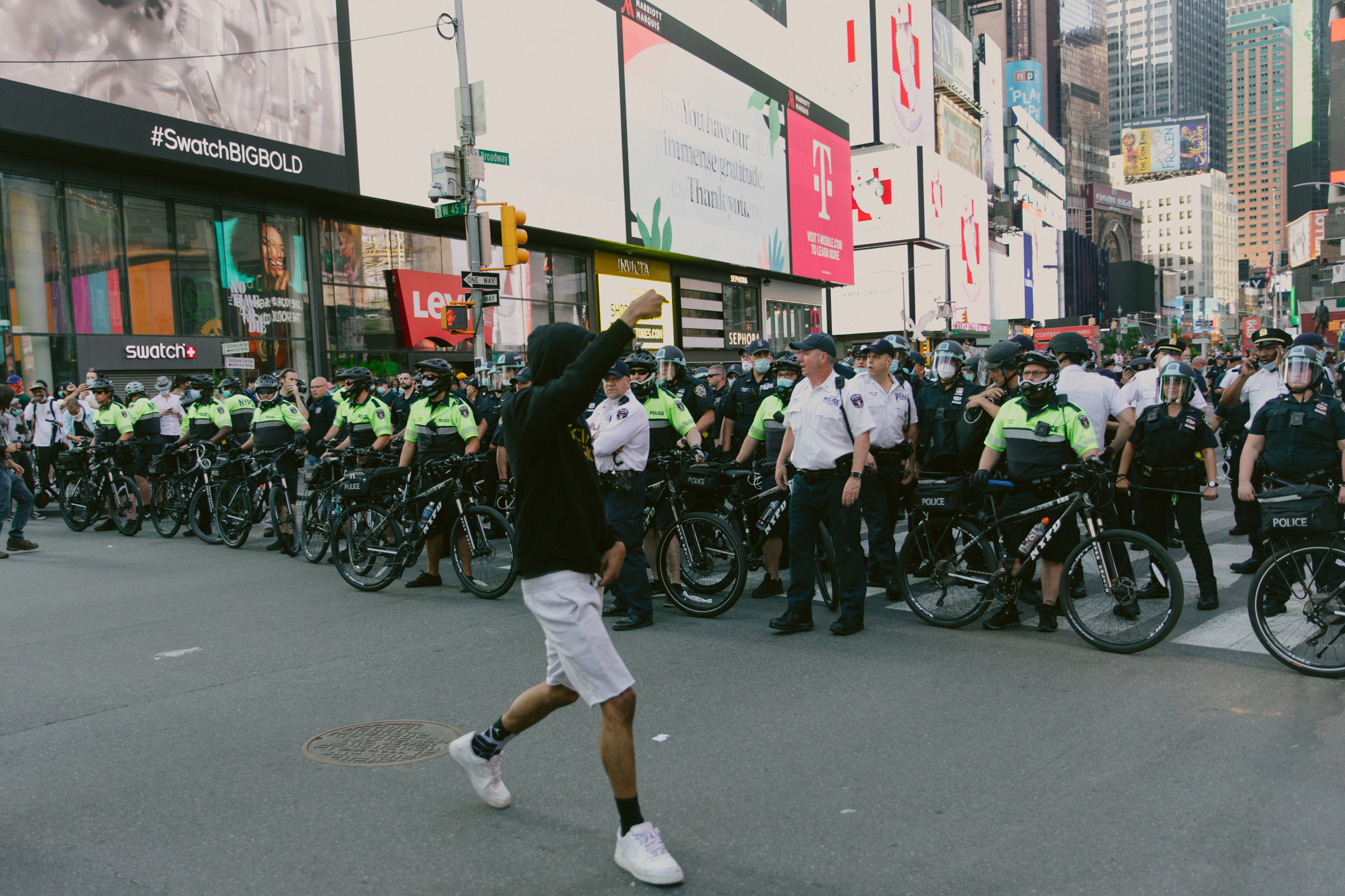 A protester walks by officers in Times Square on May 30.