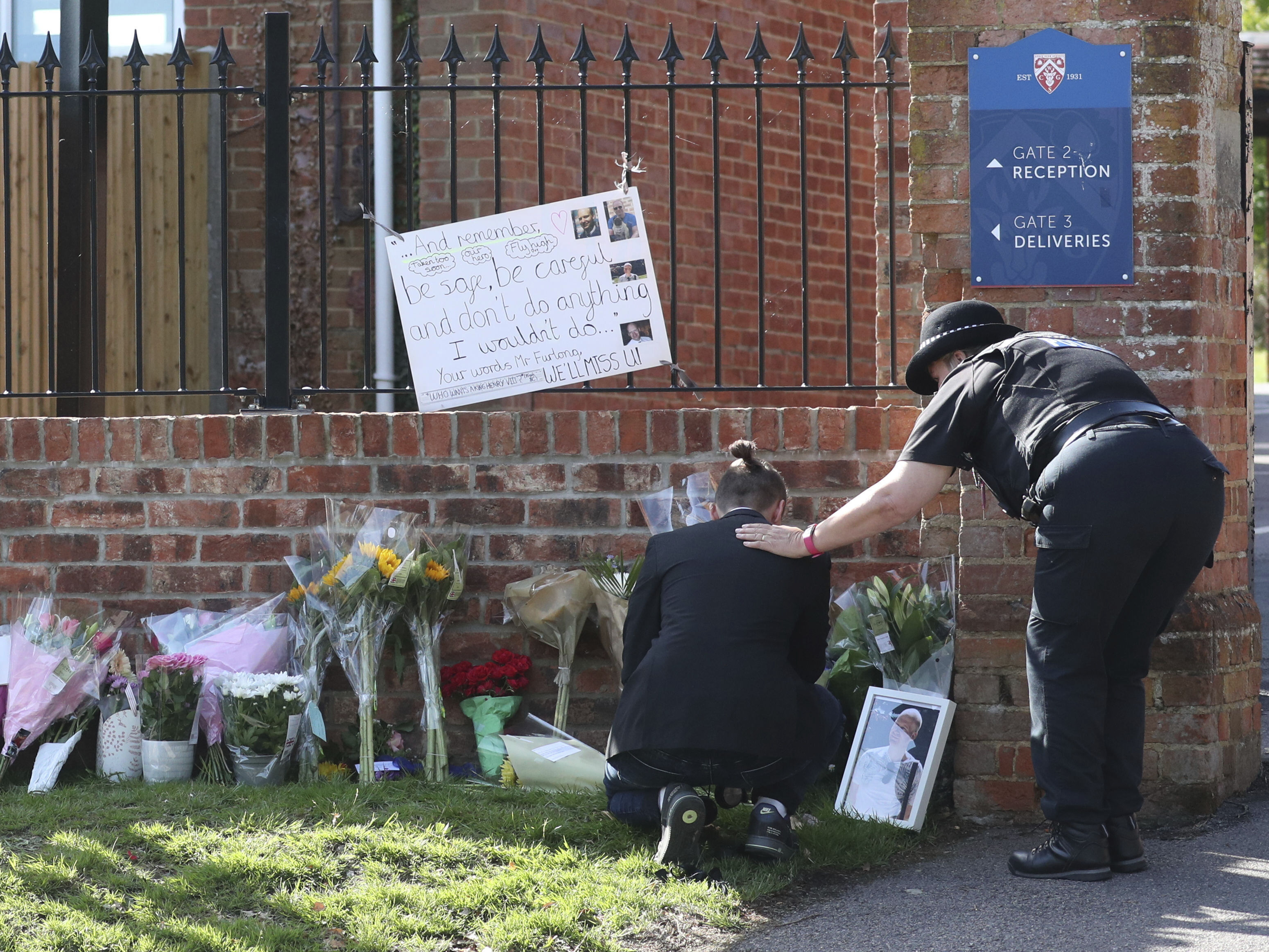A mourner is comforted by a police officer as tributes are placed at the entrance to Holt School in Wokingham, England on June 22, 2020. A teacher at the school was killed in a stabbing attack in nearby Reading.