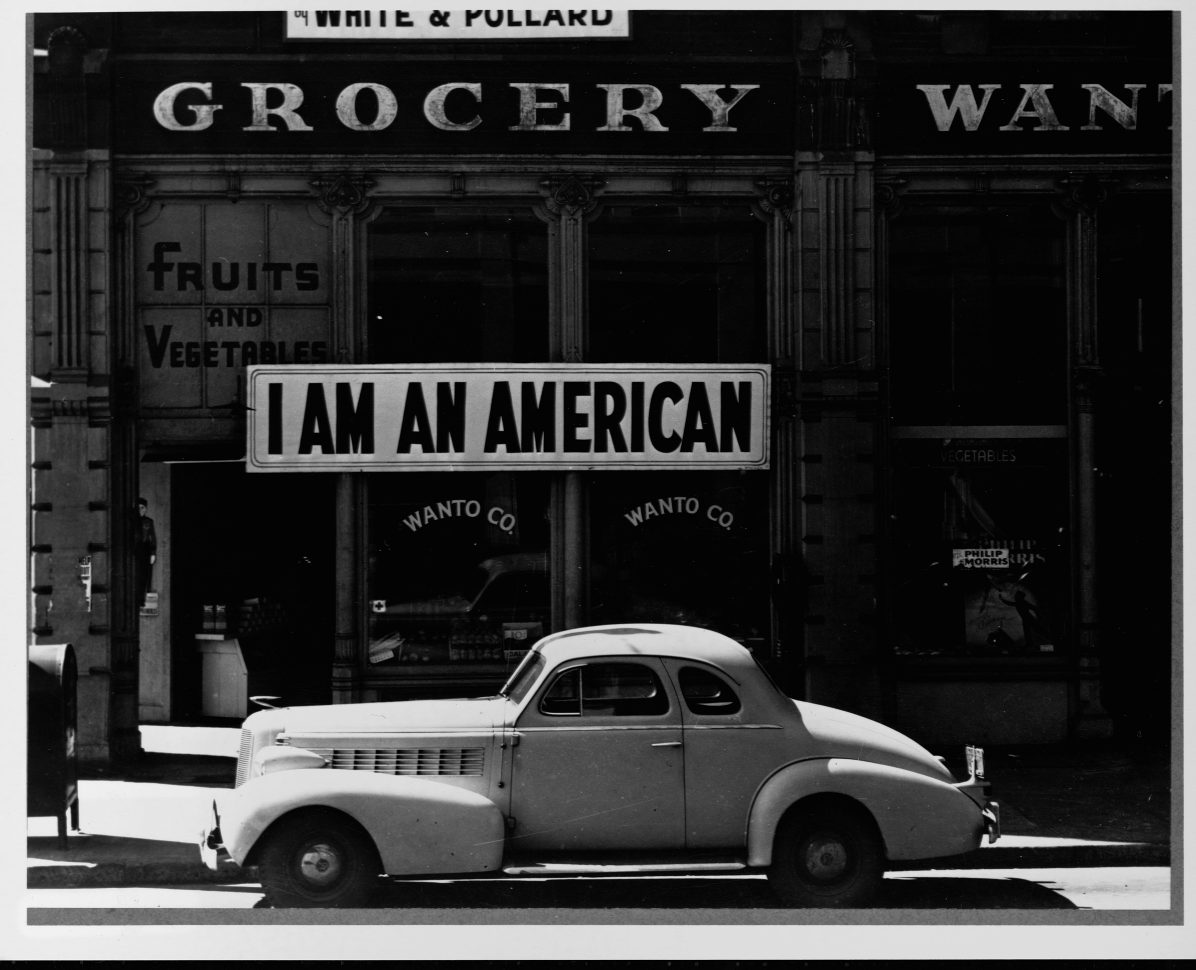 The Japanese owner of this grocery store in Oakland, California displays a sign reminding pedestrians of his loyalties to America, and not Japan, in 1944.