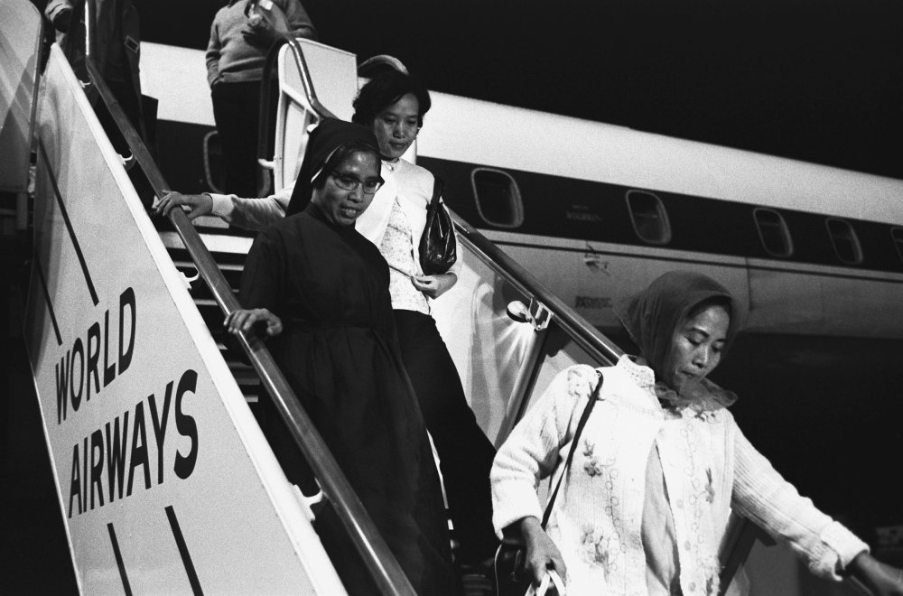 Refugees from Vietnam descend a flight of stairs from an airplane in Oakland, California, April 1975