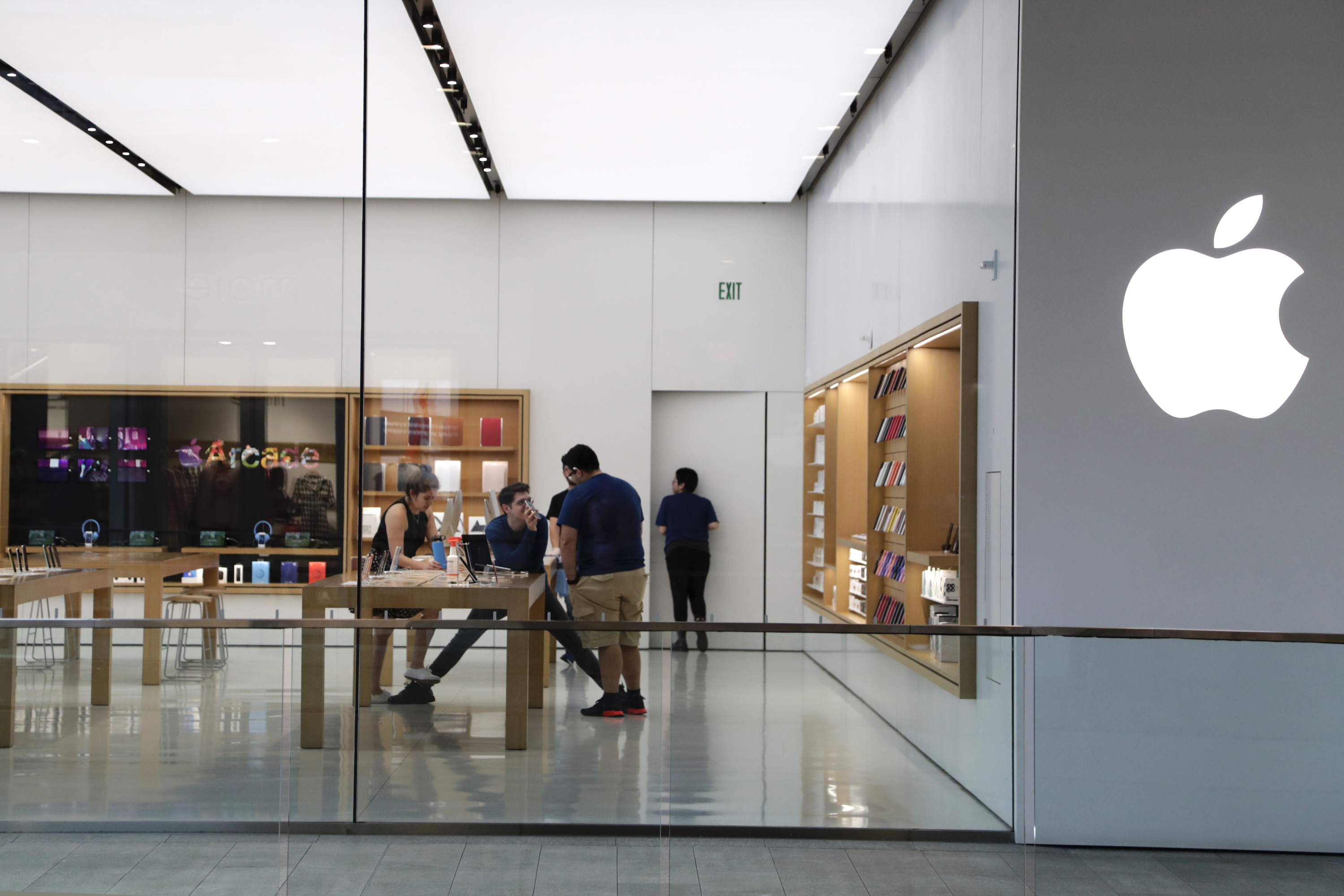 Apple employees work inside a closed Apple store in Miami on March 14, 2020.