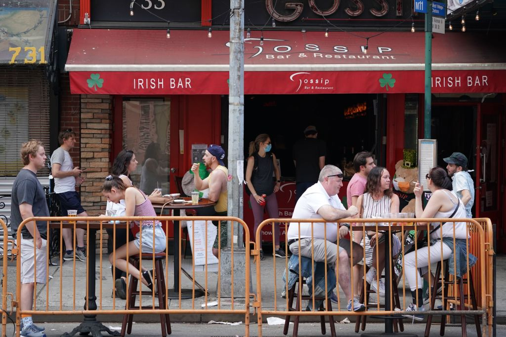 People drink outdoors at bars and restaurants in the Hells Kitchen neighborhood of New York on June 7, 2020.