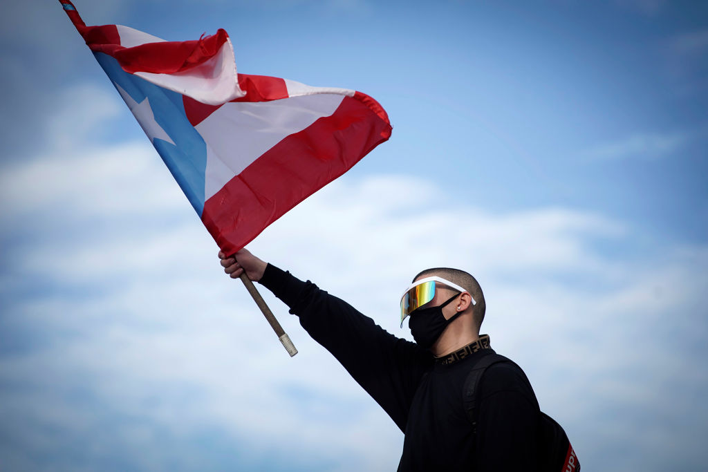 Puerto Rican reggaeton singer Bad Bunny waves a Puerto Rican flag as he takes part of a demonstration demanding Governor Ricardo Rossello's resignation in San Juan, Puerto Rico on July 17, 2019.