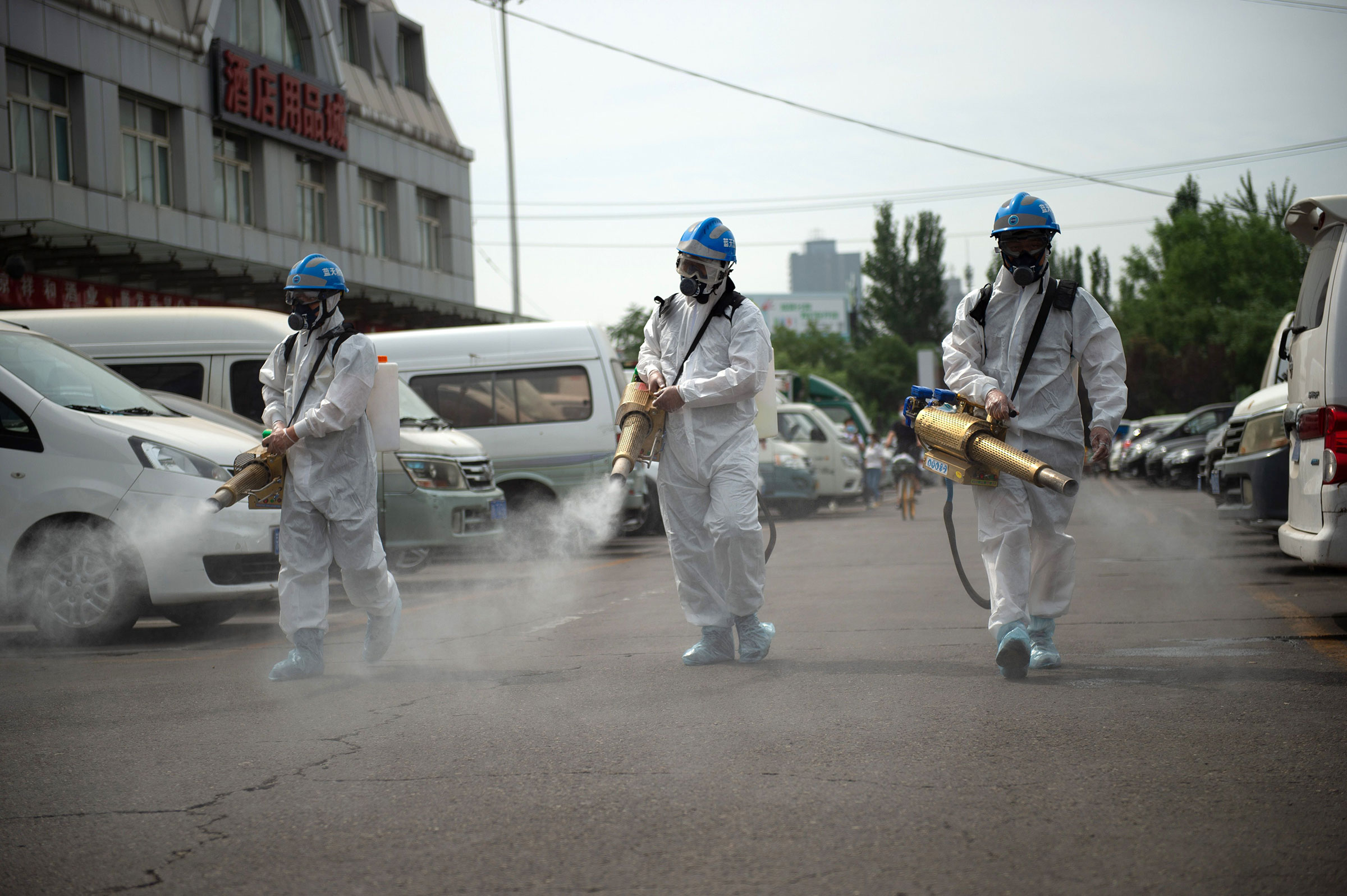 Members of the Beijing Blue Sky Rescue team conduct disinfection at the Yuegezhuang wholesale market in Beijing on June 16, 2020.