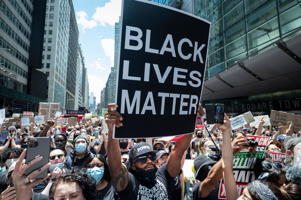 A protester in Times Square holds up a large sign that reads,  Black Lives Matter  with thousands of people behind him on June 7, 2020.
