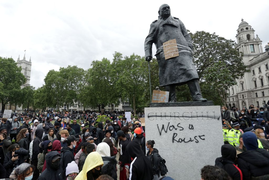 The statue of former British prime minister Winston Churchill is seen defaced, with the words (Churchill)  was a racist  written on its base in Parliament Square, central London after a demonstration outside the U.S. Embassy, on June 7, 2020, organized to show solidarity with the Black Lives Matter movement.