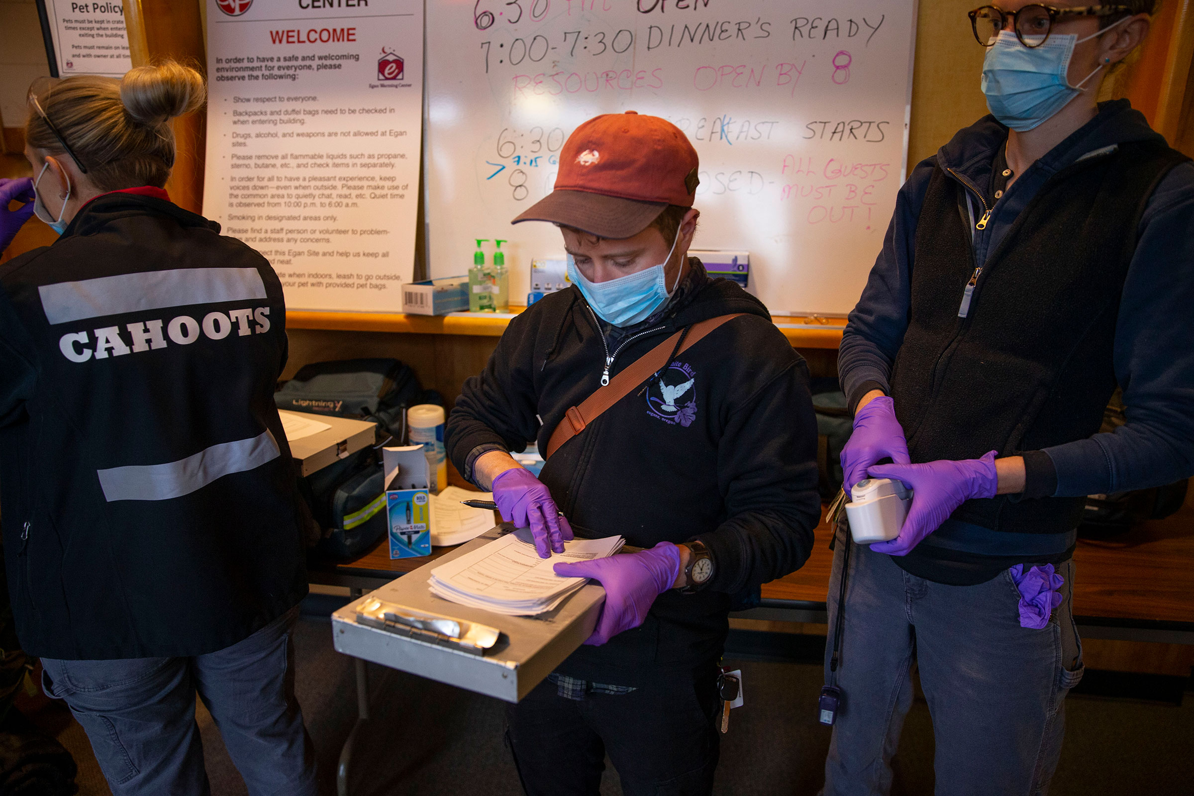 Ve Gulbrandsen, center, an EMT with CAHOOTS, joins a team from White Bird in screening guests for health concerns at the Egan Warming Center in Springfield, Ore. on March 16, 2020.