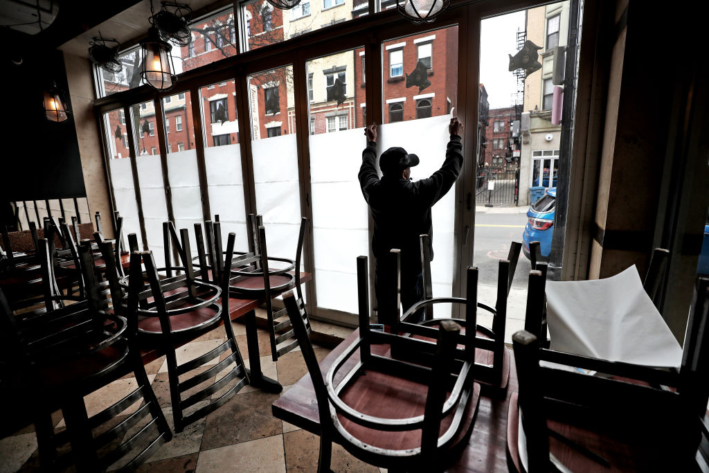 An employee of Carmelina's in the North End of Boston tapes up paper in the windows of the restaurant, which is temporarily closing during the coronavirus pandemic, on March 25, 2020.
