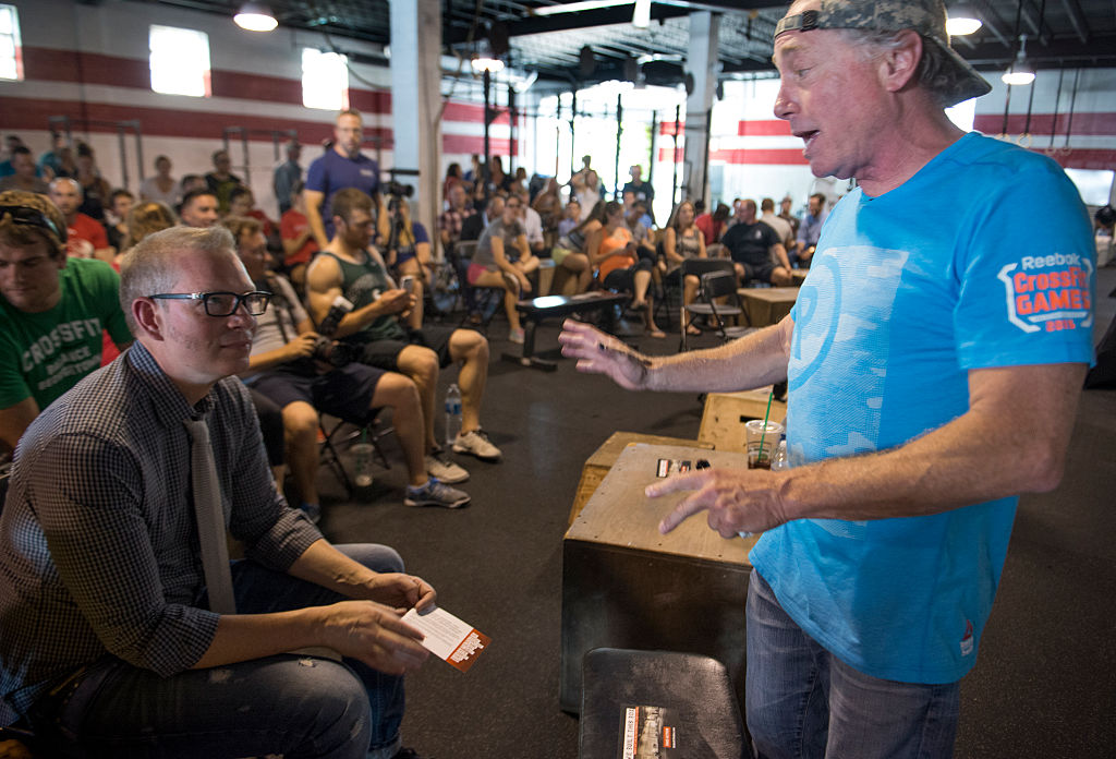 Crossfit Inc. founder and CEO Greg Glassman (R) talks to employees prior to a presentation in Washington, DC on July 31, 2015.