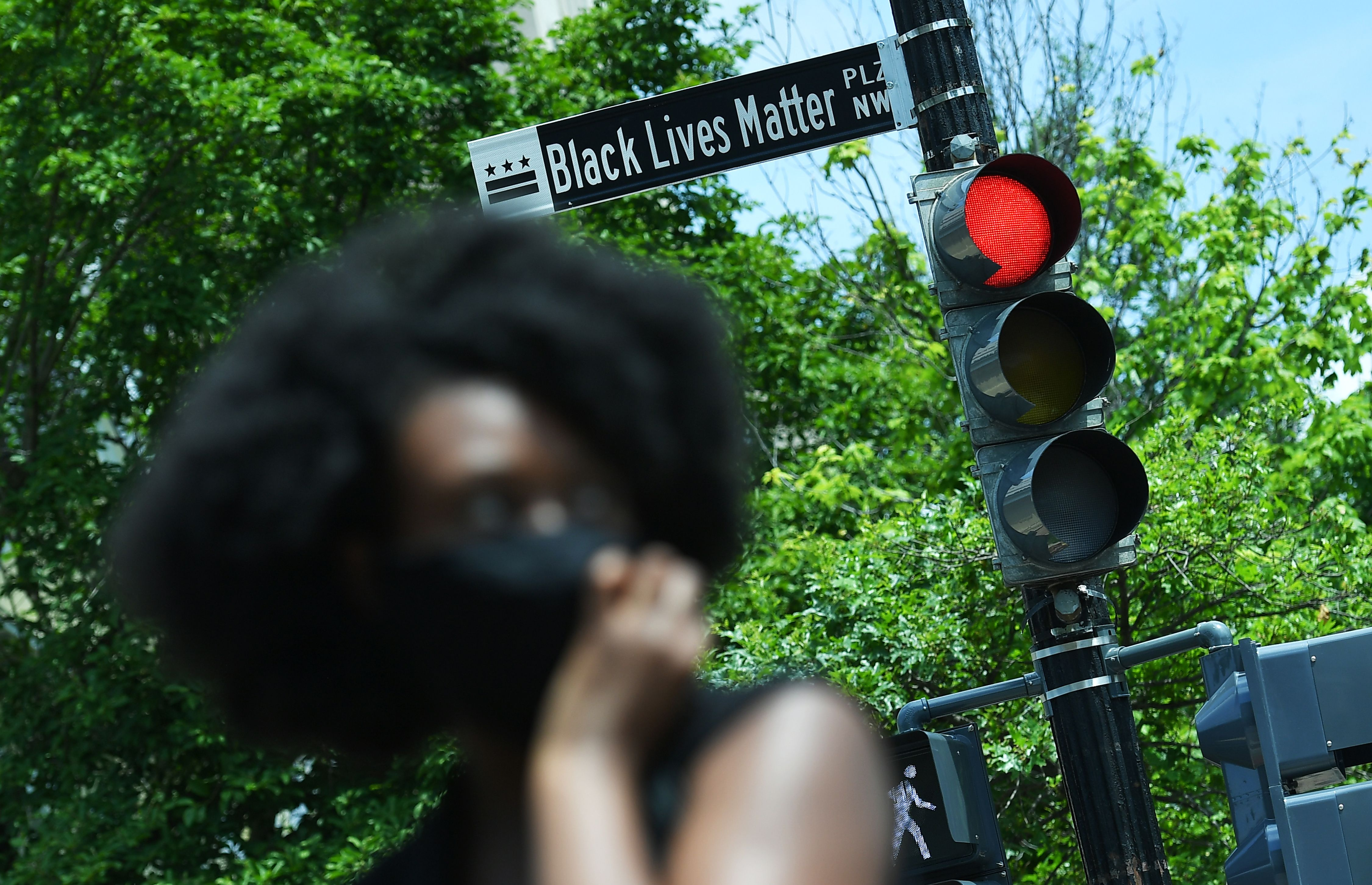 A woman is seen in front of a street sign for the newly proclaimed  Black Lives Matter Plaza  near the White House in Washington, D.C. on June 5 2020.