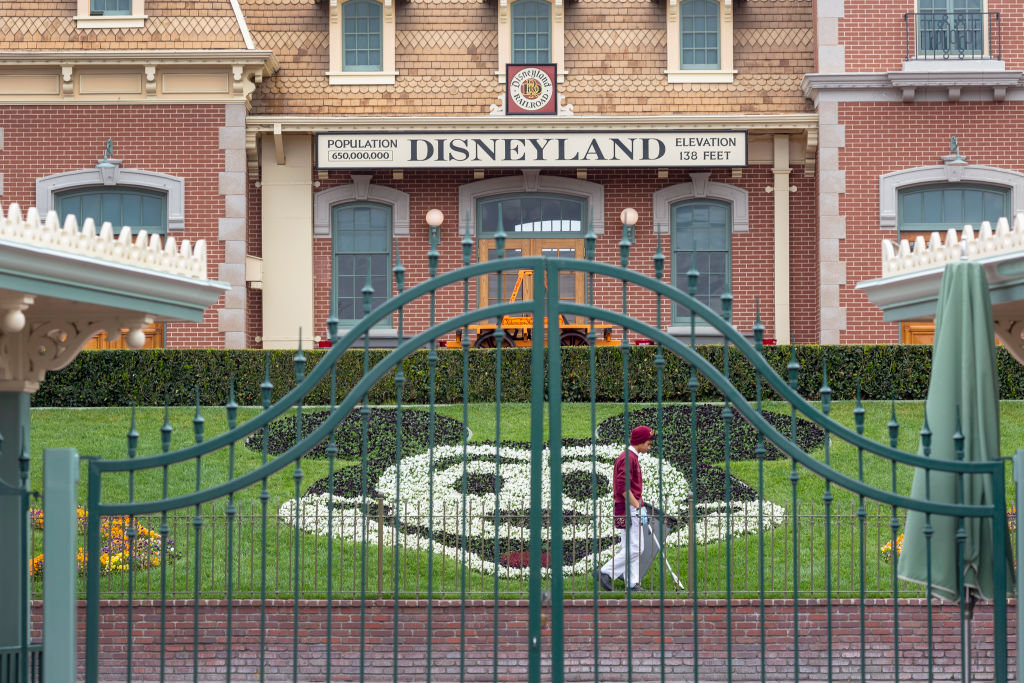 An employee cleans the grounds behind the closed gates of Disneyland Park on the first day of the closure of Disneyland and Disney California Adventure theme parks as fear of the spread of coronavirus continue, in Anaheim, California, on March 14, 2020.