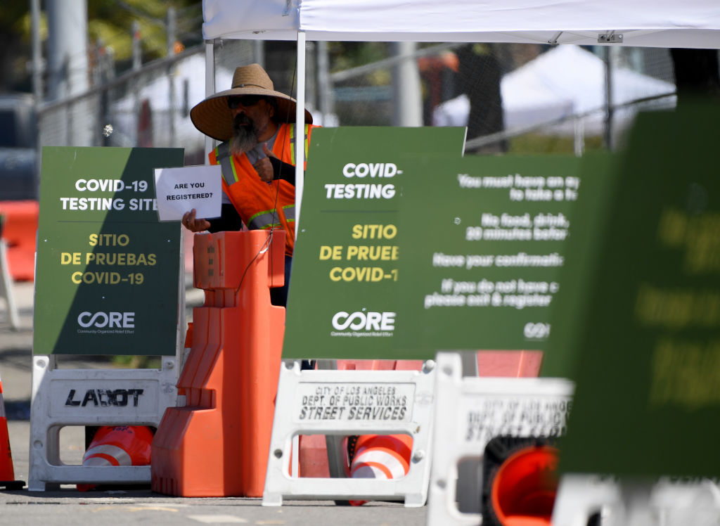 A worker holds up a sign asking for registration before entering a drive-thru COVID-19 testing facility at Dodger Stadium on May 28, 2020 in Los Angeles, California.