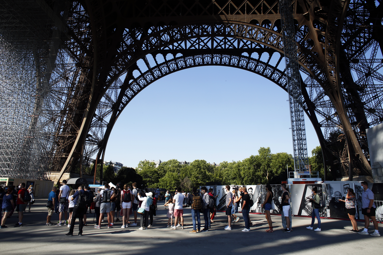 People queue up prior to visit the Eiffel Tower, in Paris, June 25, 2020.