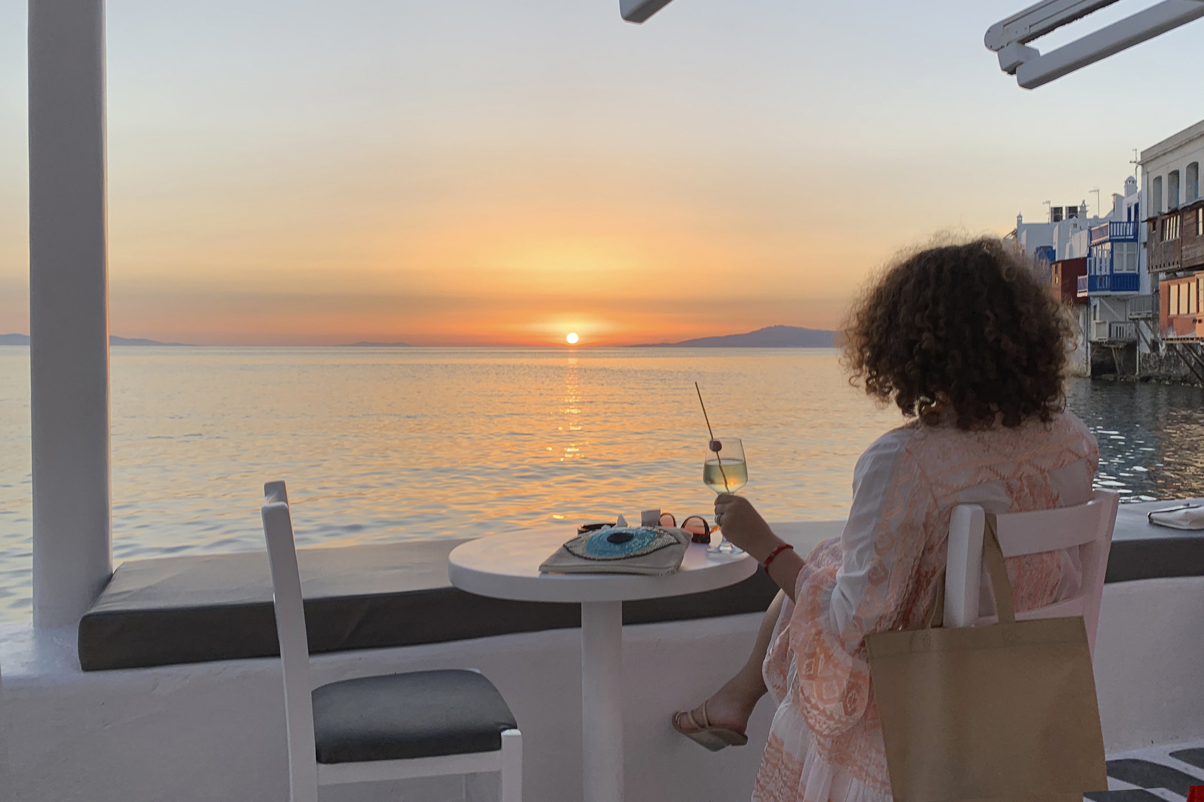 A visitor watches the sunset at a bar in an area known as Little Venice in the main town of the island of Mykonos, Greece, on June 9, 2020.