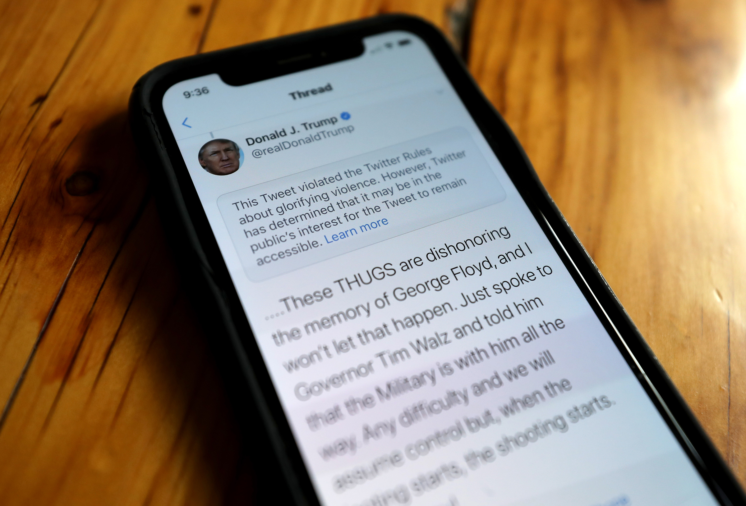 A notification from Twitter appears on a tweet by President Trump warning that it violated its policy on May 29
