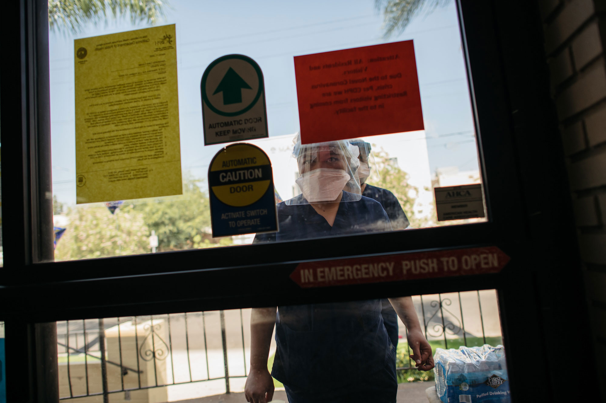 Staff members wait to be let in during shift change at Alexandria Care Center in Los Angeles.