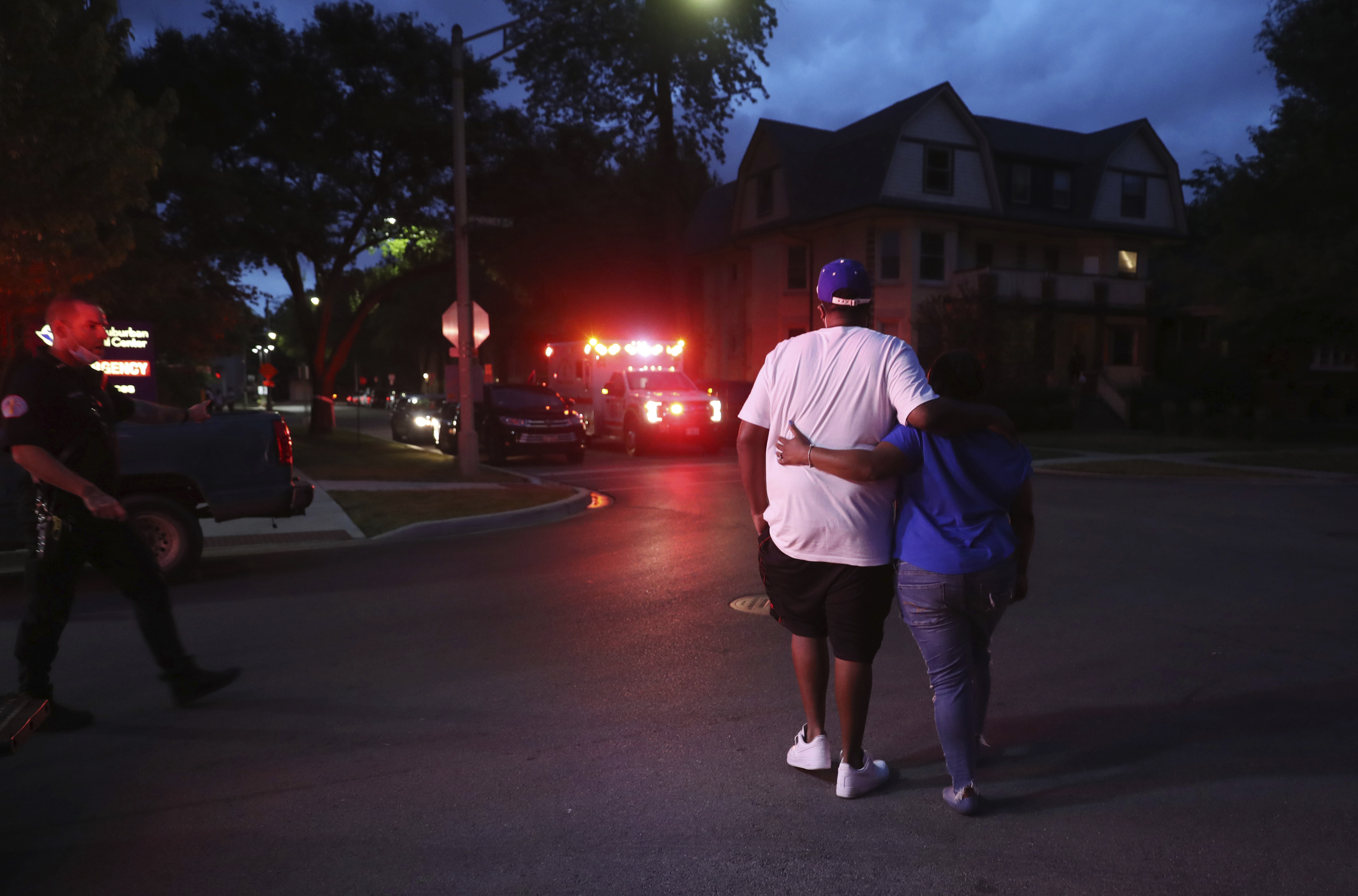 Two people walk away from West Suburban Medical Center in Oak Park, in Chicago, where a 3-year-old boy died after being shot while riding in an SUV with his father a few blocks away in the Austin neighborhood, June 20, 2020.