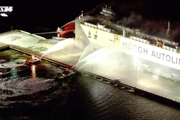 In this image made from aerial video taken on June 4, 2020, firefighters spray a cargo ship with water, in Jacksonville, Florida.