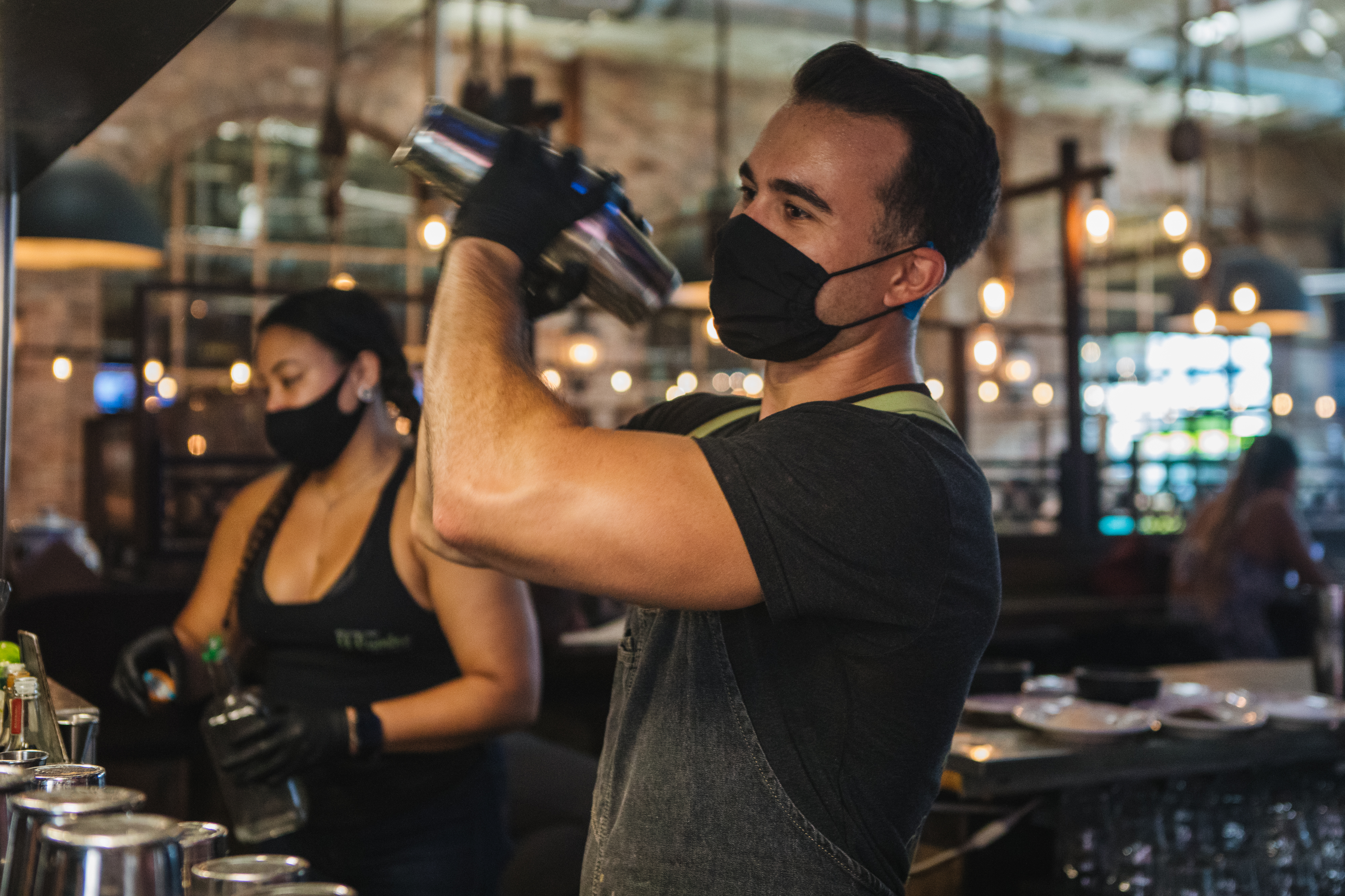 Employees wearing protective masks and gloves prepare drinks at a restaurant in Fort Lauderdale, Florida, U.S., on June 25, 2020.
