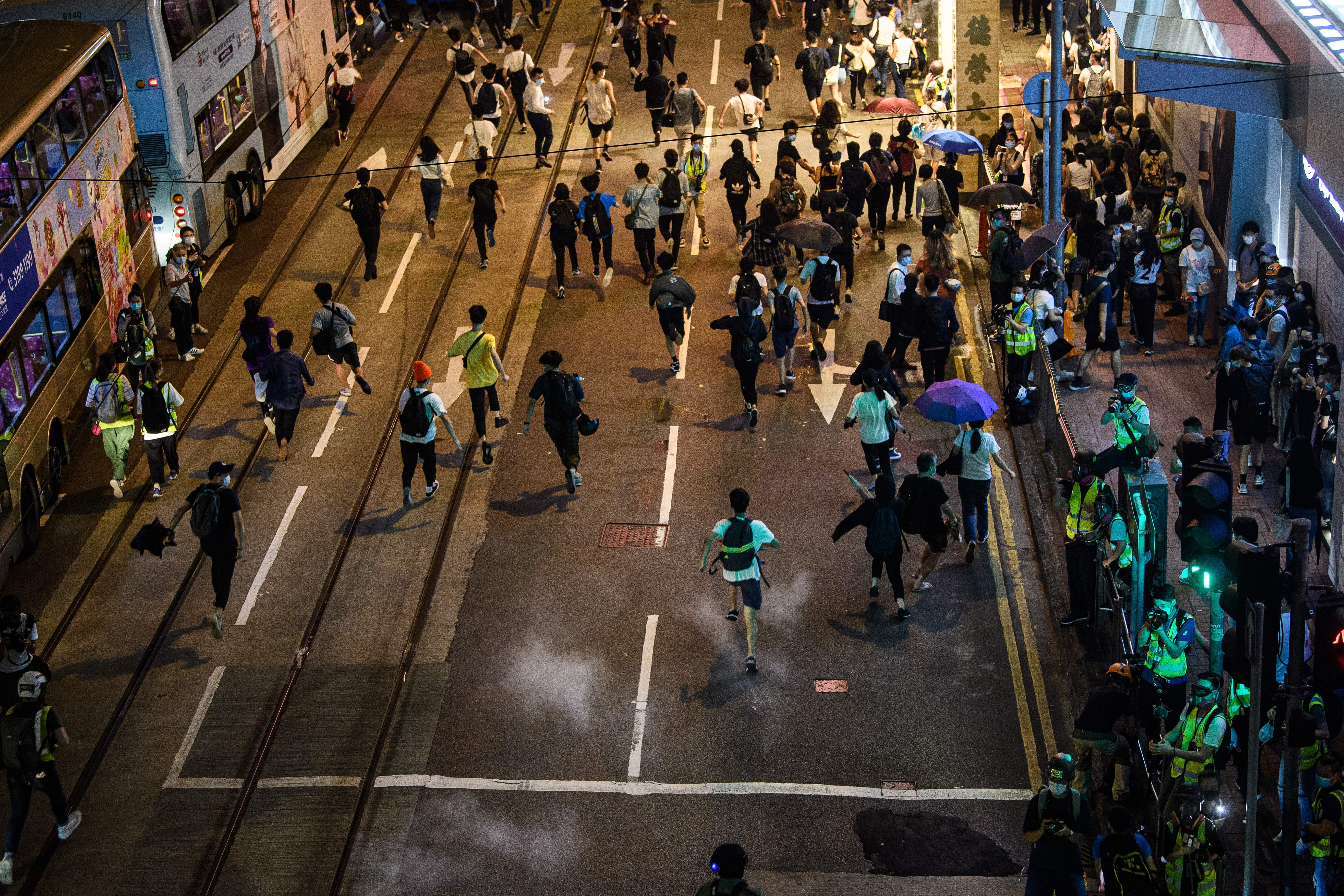 Pro-democracy protesters run as police fire pepper ball rounds to disperse the crowd in the Central district of Hong Kong on June 9, 2020, as the city marks the one-year anniversary since pro-democracy protests erupted