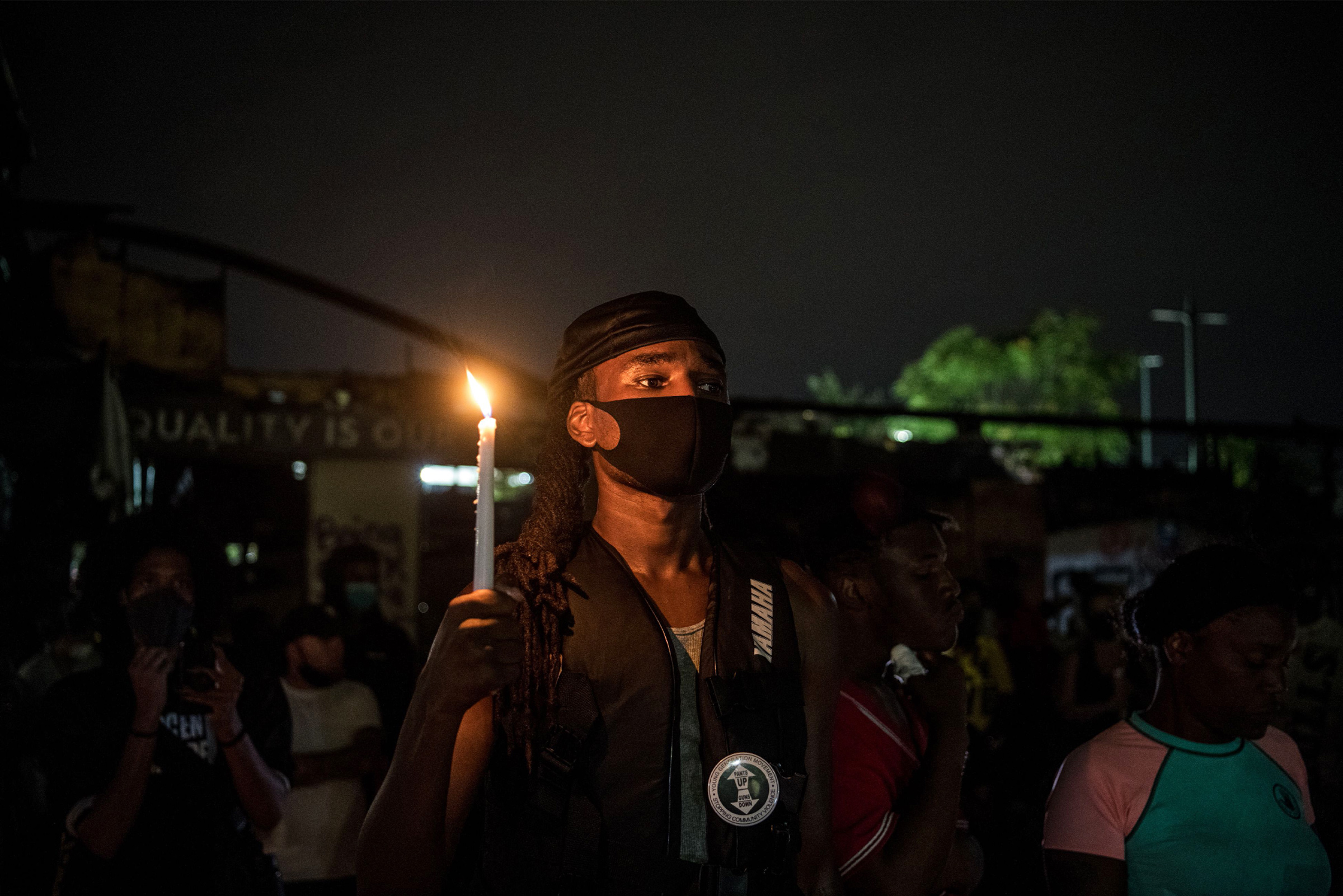 A protester holds a candle following Rayshard Brooks' death in Atlanta, on June 15