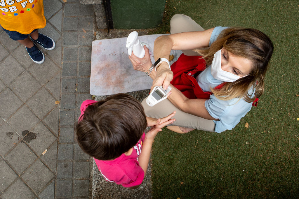 A child has their temperature checked by a member of staff before entering English For Fun school in Madrid on June 24, 2020.