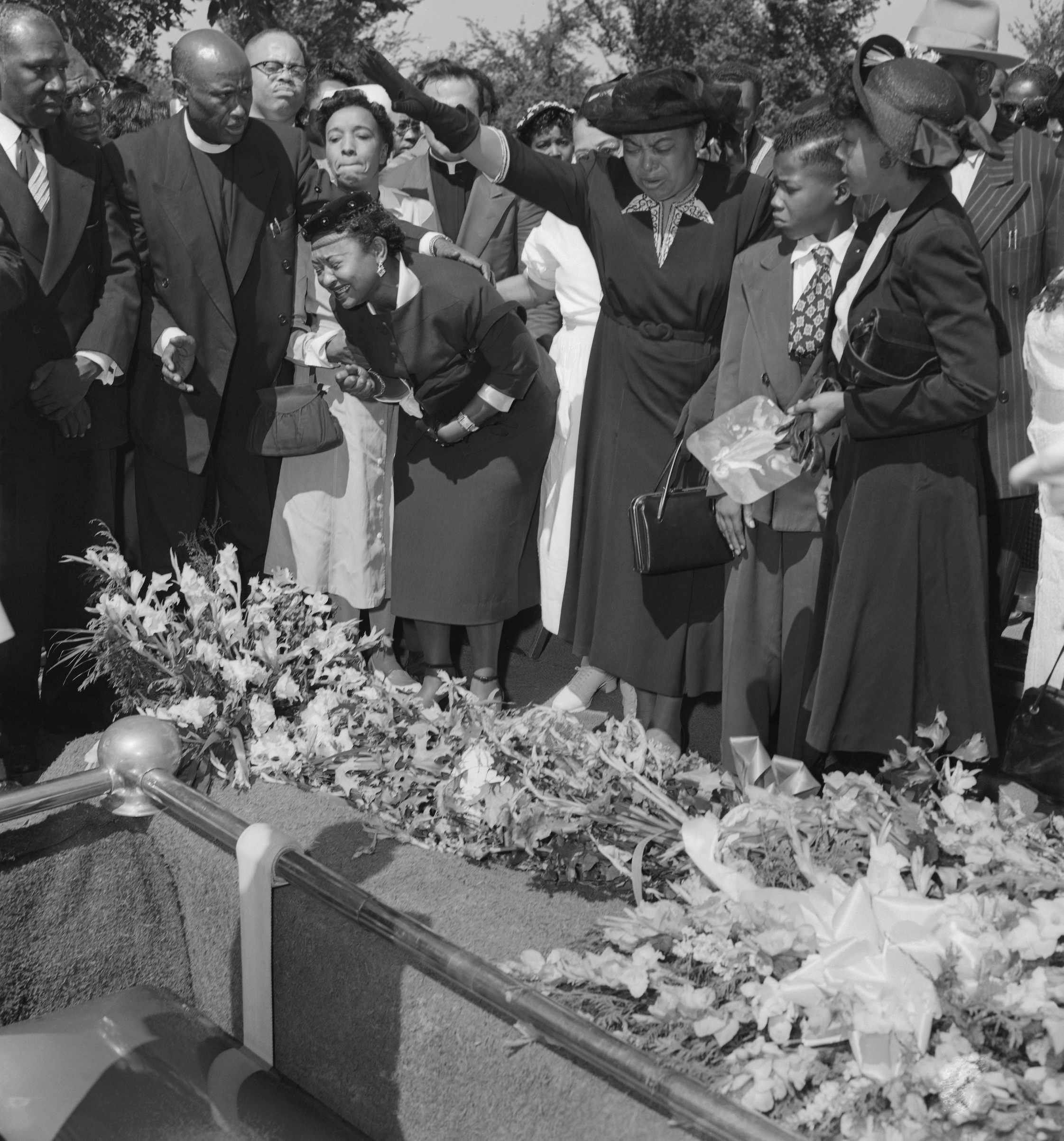 Friends restrain Emmett Till's grief-stricken mother (left) as her son's body is lowered into the grave.