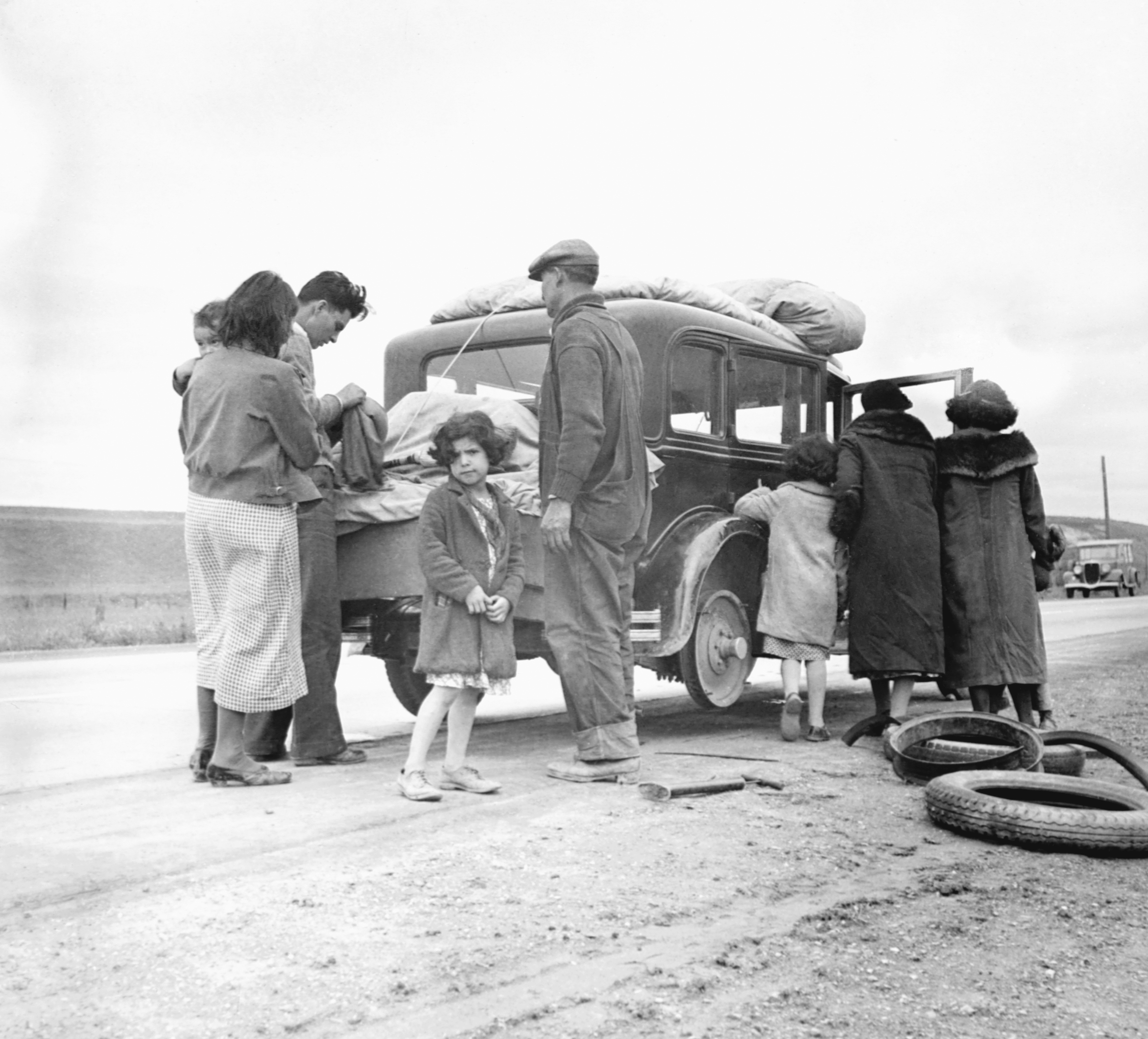 Migrant family from Mexico fixing a tire in California, February 1936.