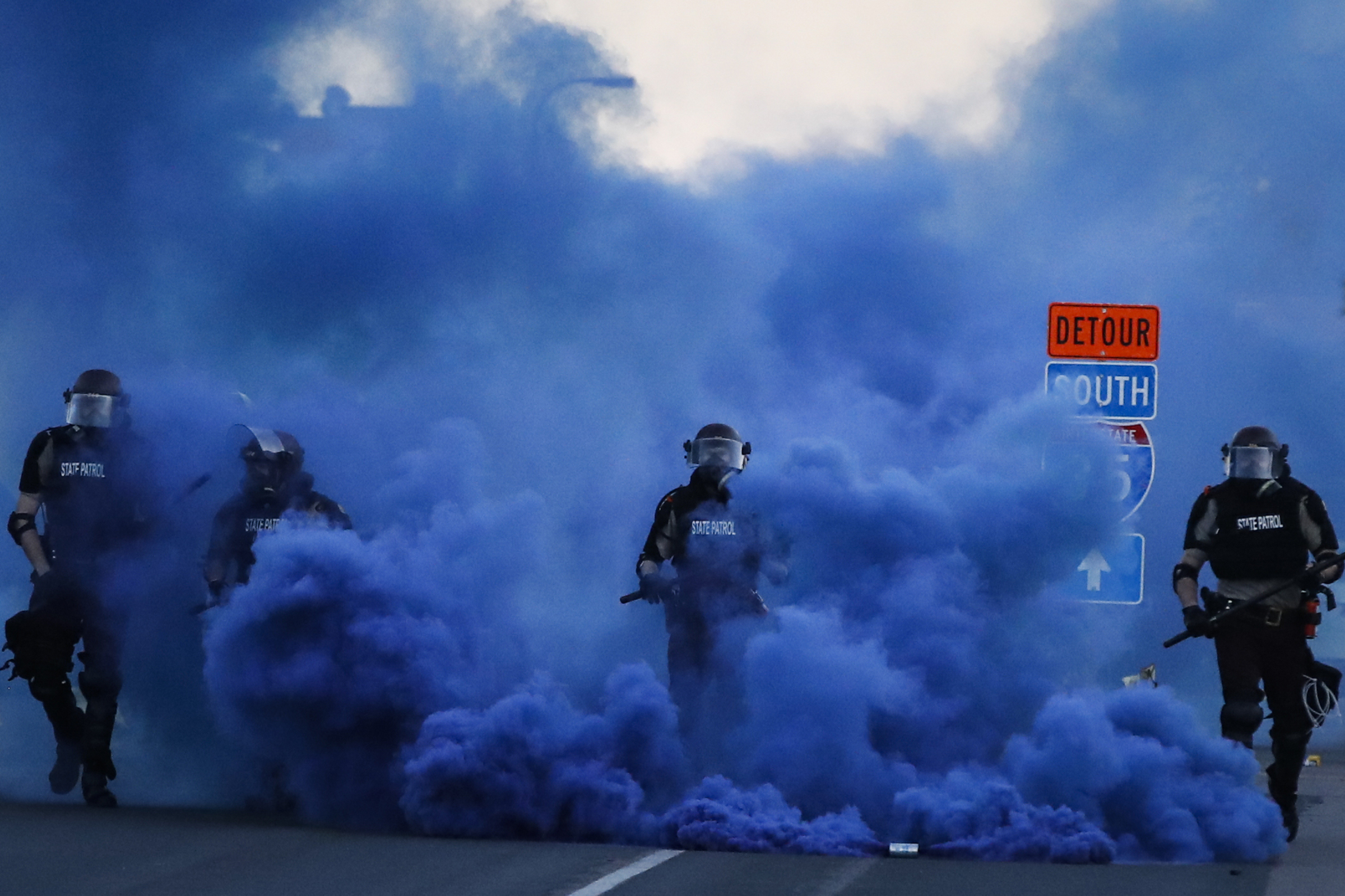 Police in riot gear walk through a cloud of blue smoke as they advance on protesters near the Minneapolis 5th Precinct, on May 30, 2020.