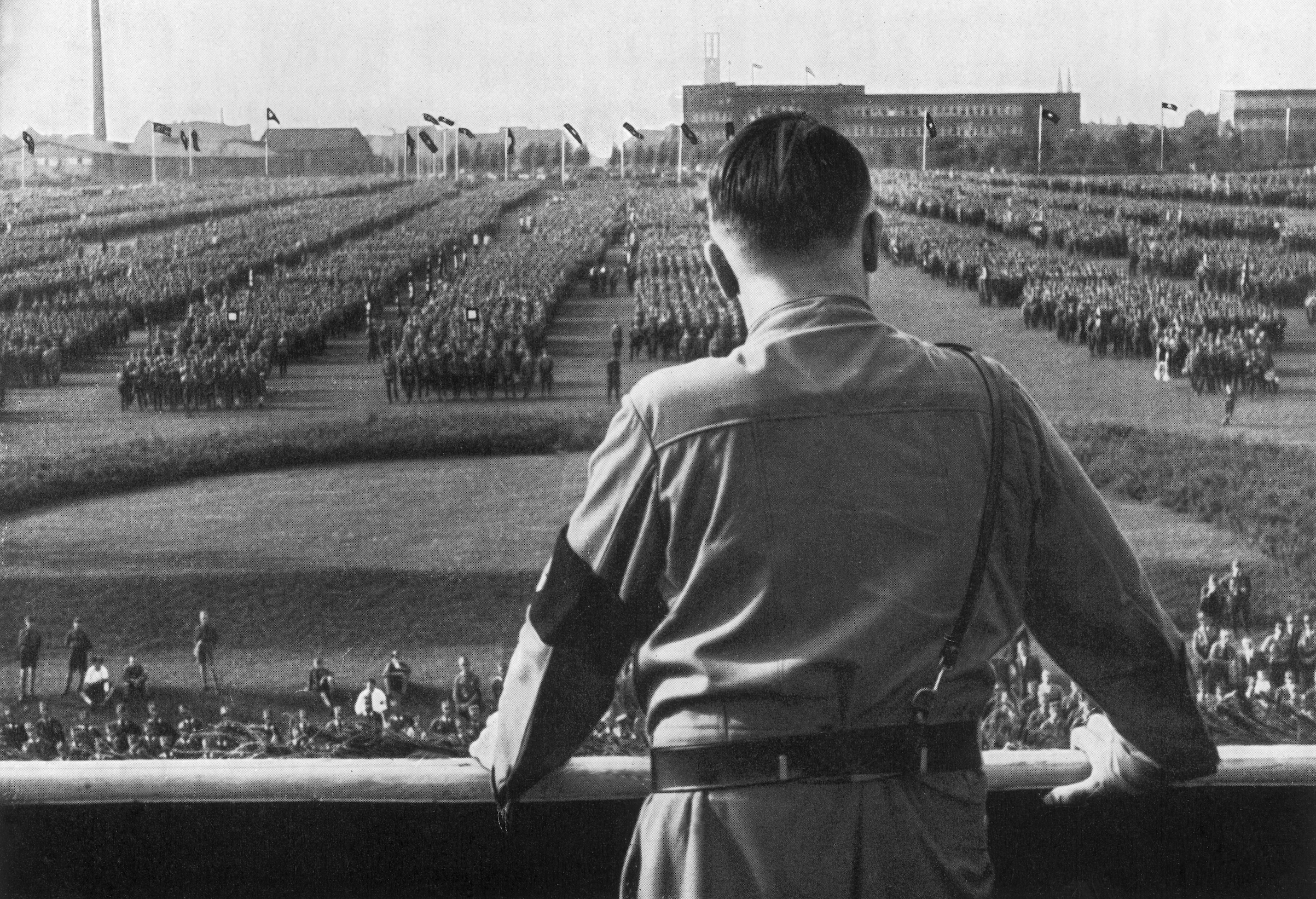 Nazi leader Adolf Hitler addresses soldiers with his back facing the camera at a Nazi rally in Dortmund, Germany, in 1933.